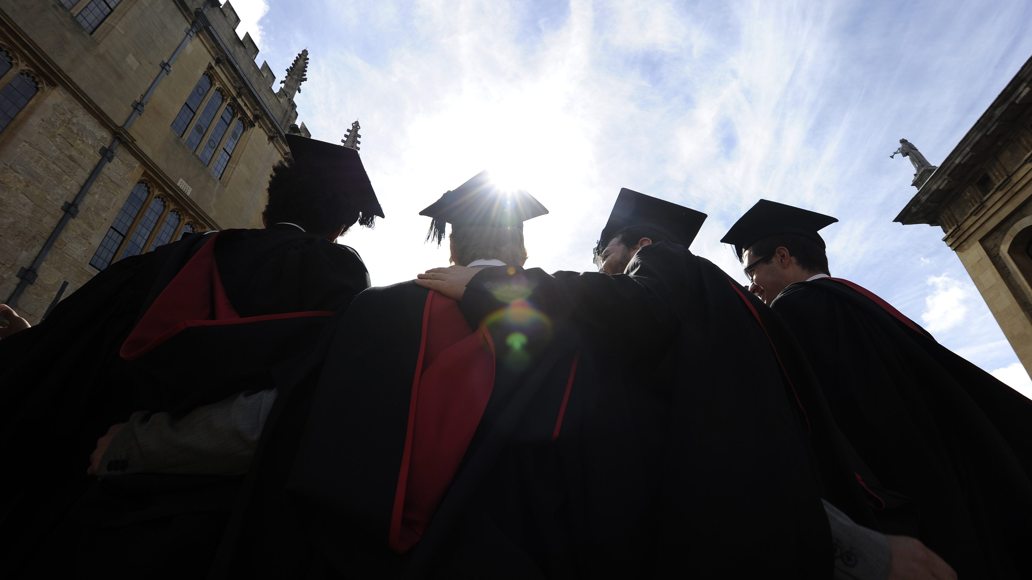 A group of graduates gather outside the Sheldonian Theatre after a graduation ceremony at Oxford University England