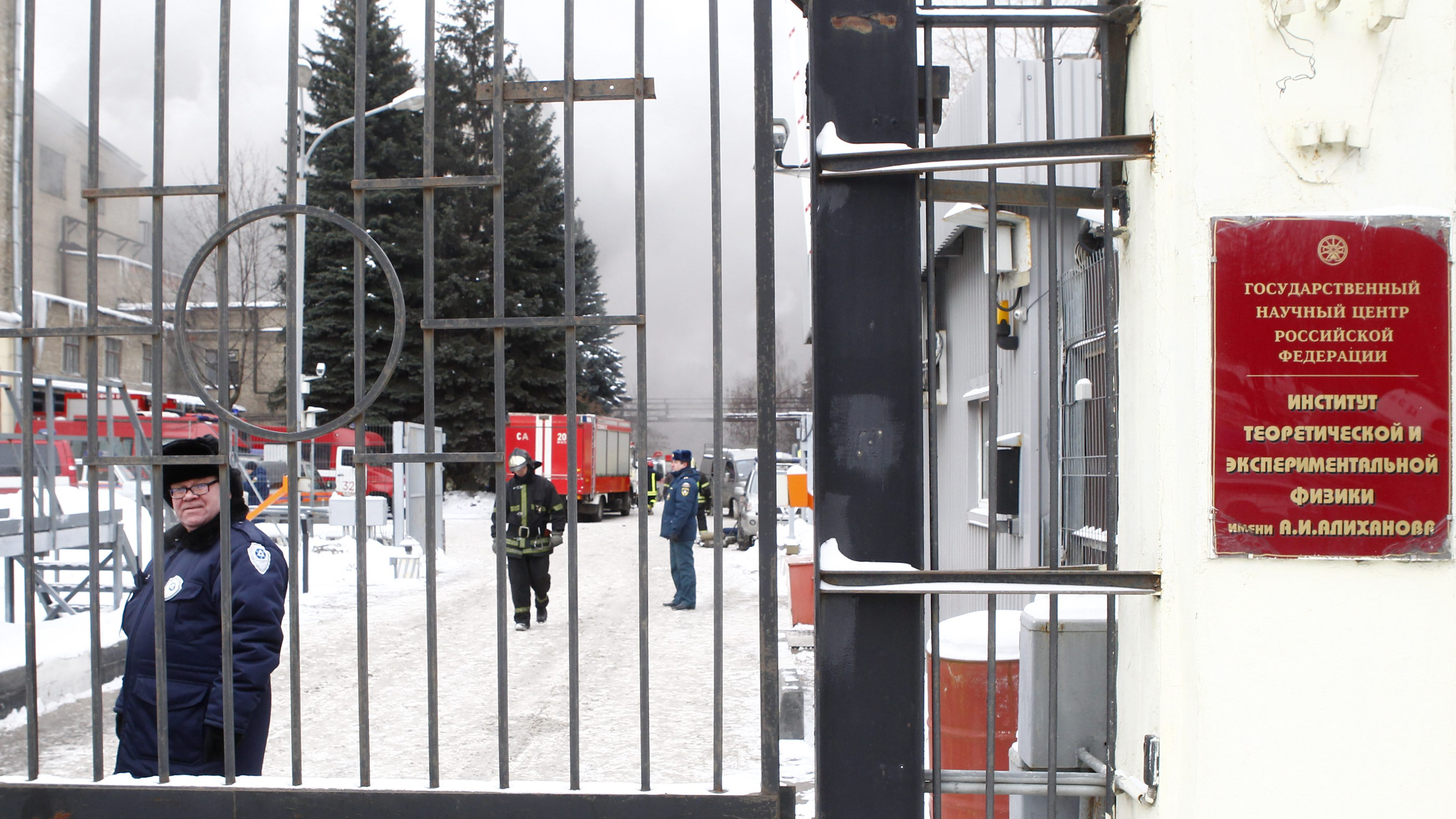A gatekeeper looks from inside the Institute of Theoretical and Experimental Physics as heavy smoke is seen in the background in Moscow