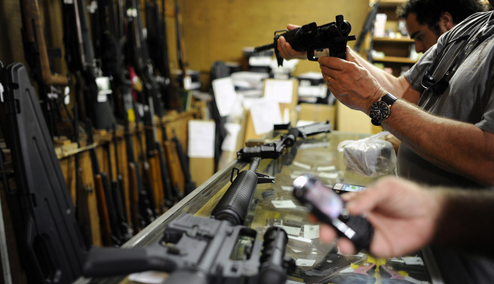 Customers look over the last two AR-15 style rifles for sale inside the Bullet Hole gun shop, as gun enthusiasts start to crowd into the shop before an expected gun control announcement by U.S. President Barack Obama, in Sarasota, Florida January 16, 2013. U.S. Vice President Joe Biden and other members of Obama's cabinet have held a series of meetings with officials in the weapons and entertainment industry as part of a task force requested by the president after the December 14 school shooting in Newtown, Connecticut, in which 20 children and six adults were killed.  REUTERS/Brian Blanco  (UNITED STATES - Tags: SOCIETY POLITICS) - GM1E91H028501