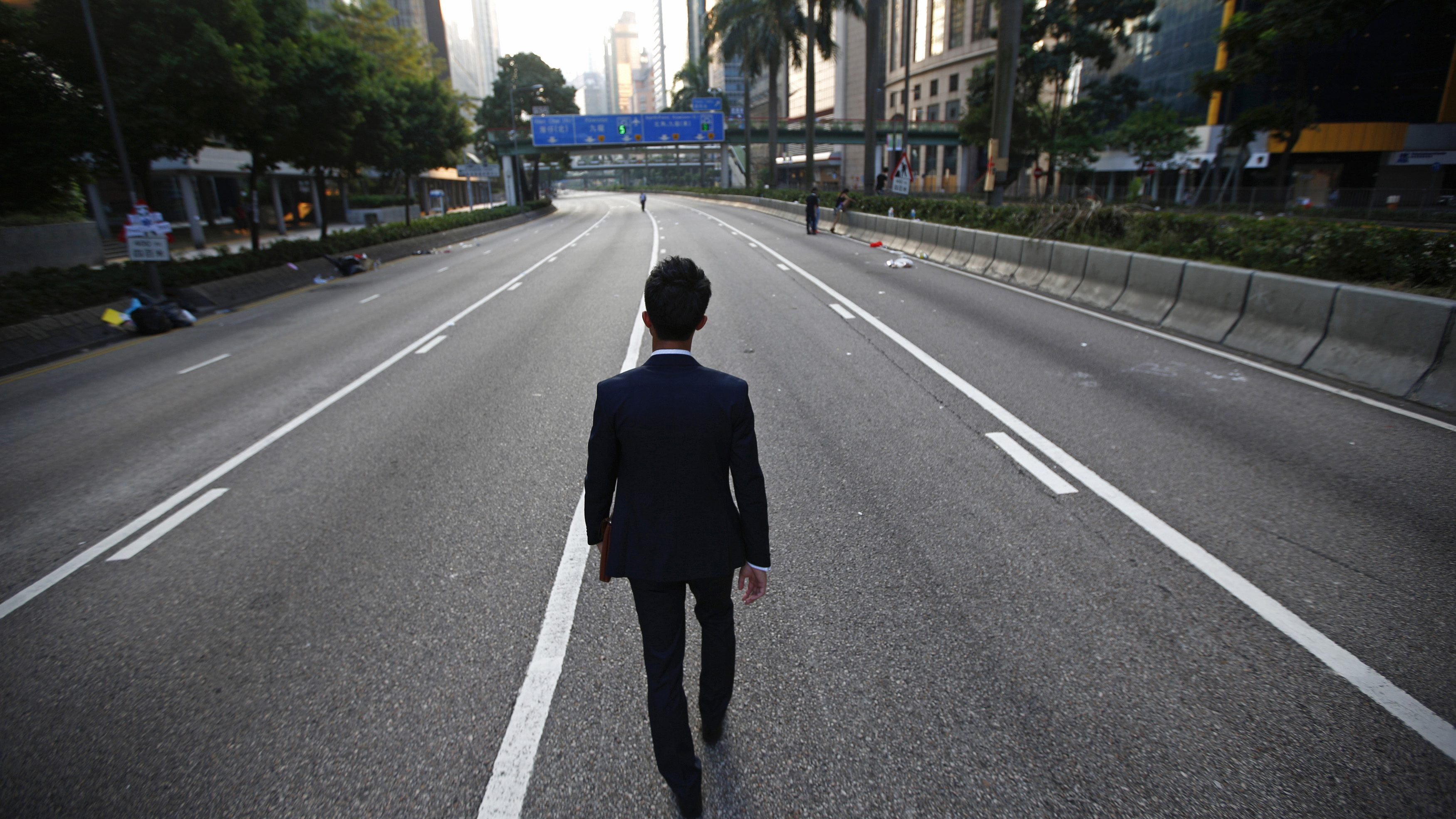 A man walks along an empty street near the central financial district in Hong Kong September 30, 2014. Tens of thousands of pro-democracy protesters extended a blockade of Hong Kong streets on Tuesday, stockpiling supplies and erecting makeshift barricades ahead of what some fear may be a push by police to clear the roads before Chinese National Day.   (CHINA - Tags: POLITICS CIVIL UNREST) - GM1EA9U0PXM01