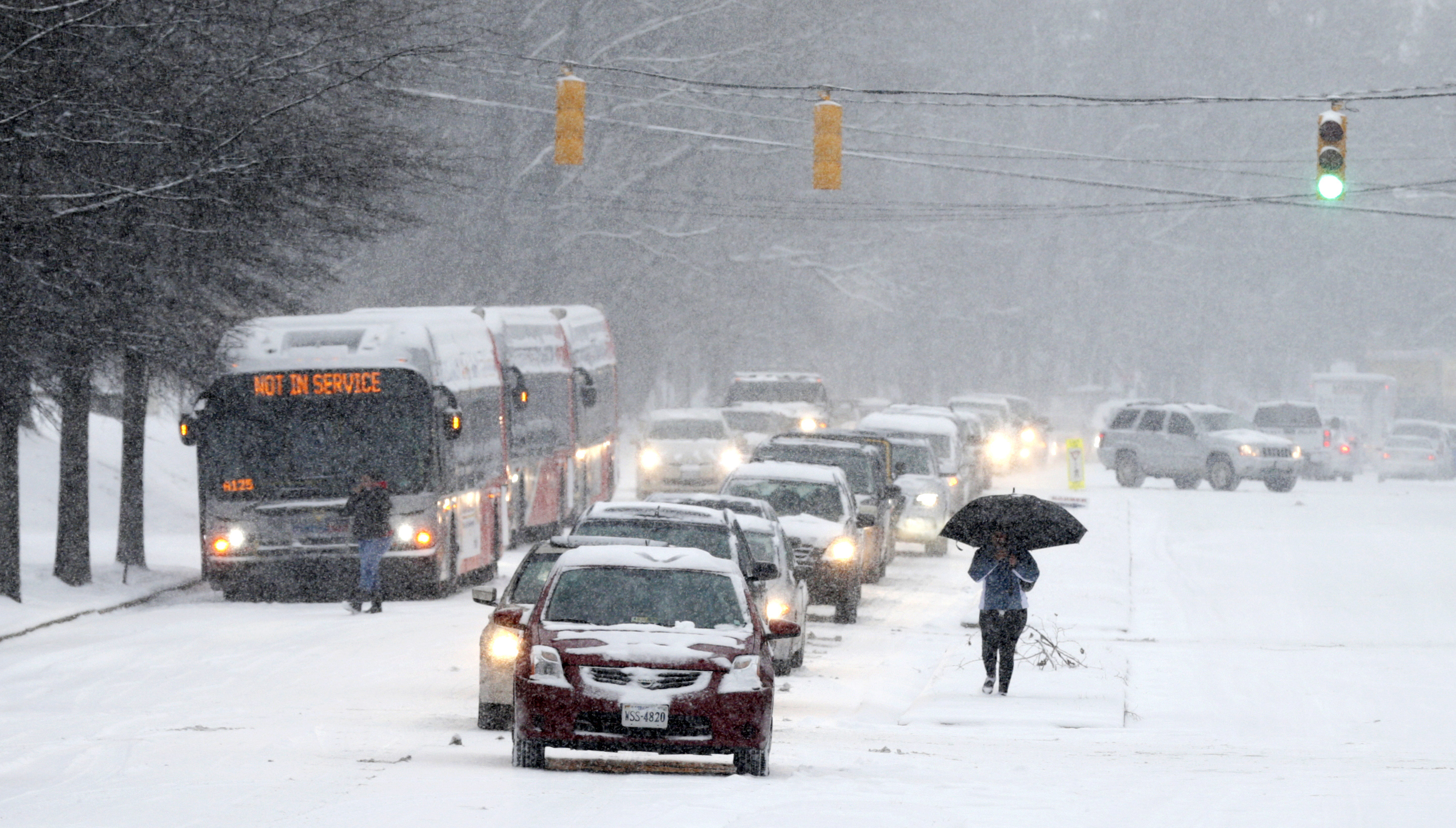 A pedestrian holding an umbrella passes by cars and a bus stopped after police closed off a stretch of Wilson Boulevard due to icy conditions in Arlington, Virginia.