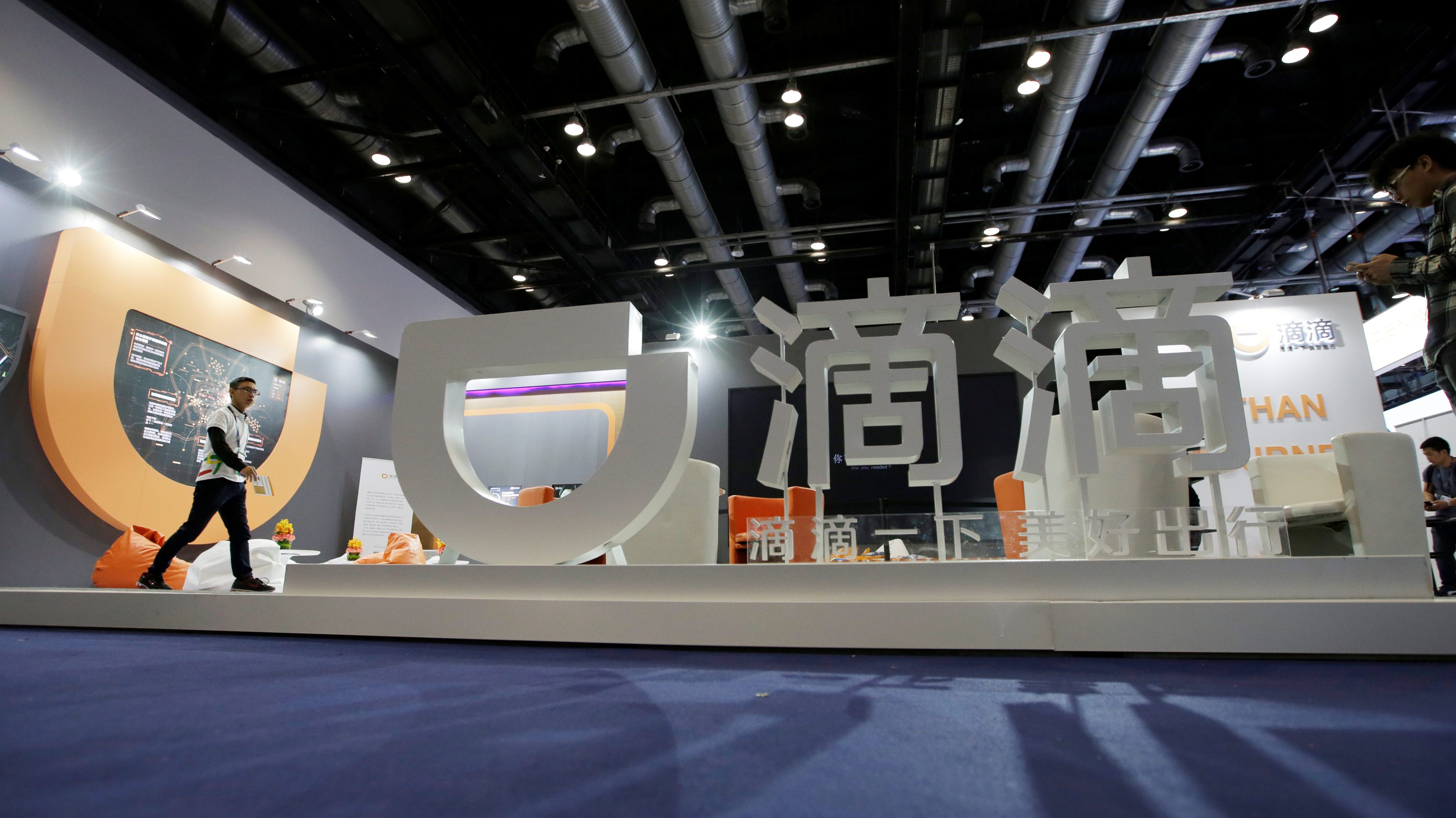 A staff member walks at Didi Chuxing's booth at the Global Mobile Internet Conference (GMIC) 2017 in Beijing, China April 28, 2017.