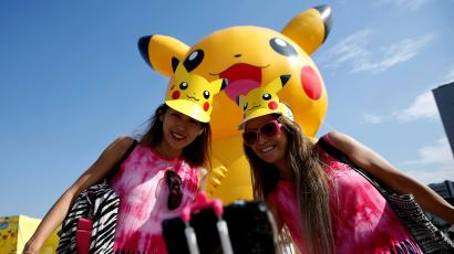 Women take a selfie in front of a large Pikachu figure at a Pokemon Go Park event in Yokohama