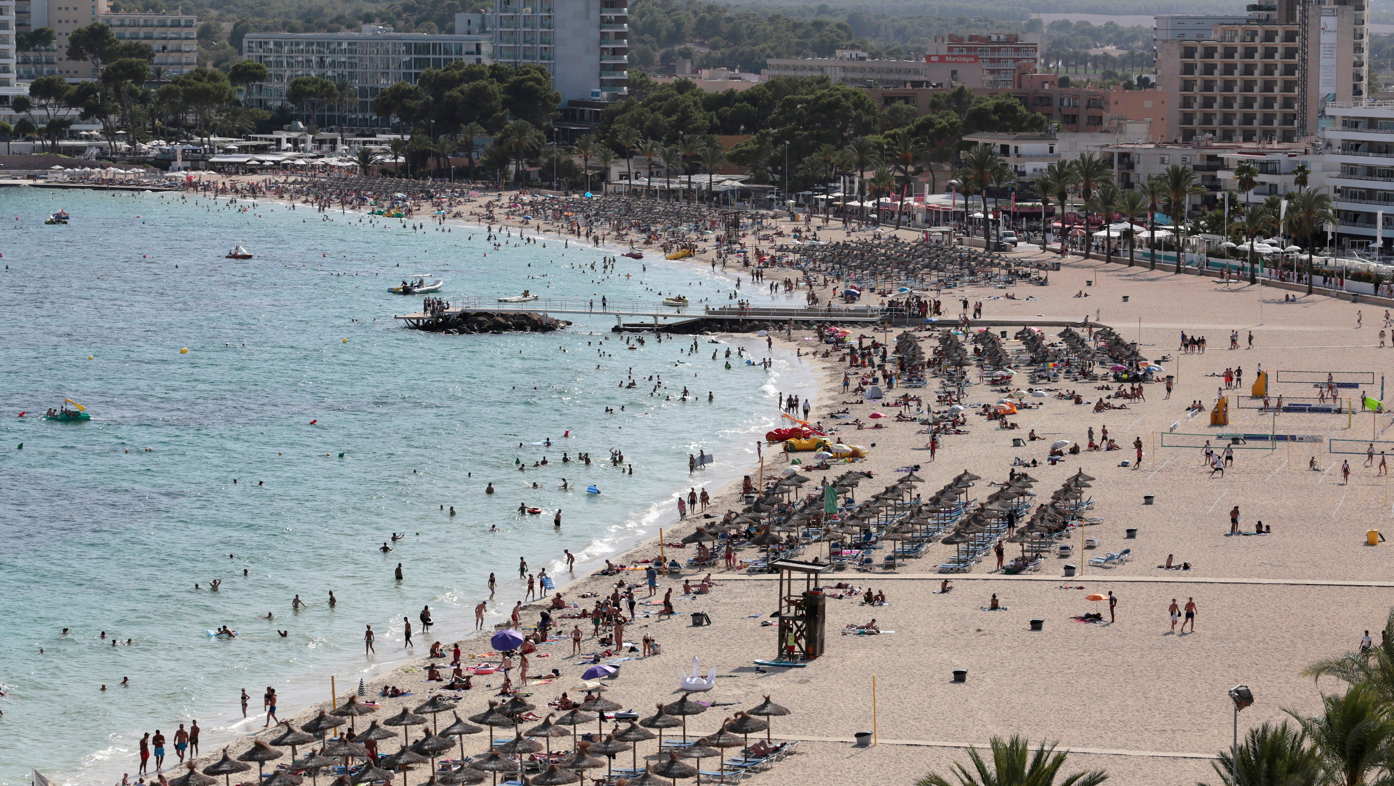 Tourists sunbathe and swim at the beach of Magaluf on the island of Mallorca, Spain, August 19, 2017.