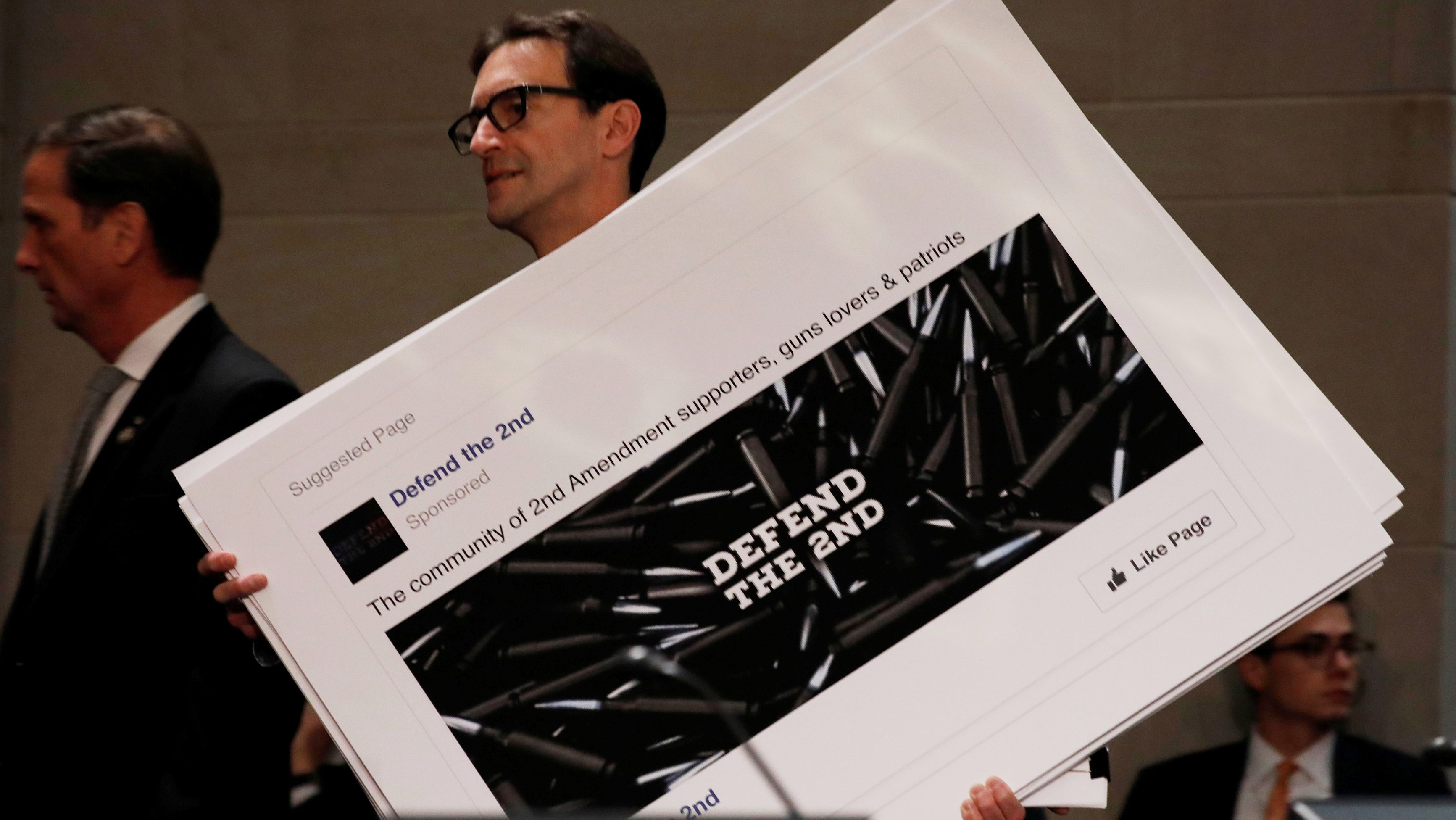 An aide puts out examples of Facebook pages, as executives appear before the House Intelligence Committee to answer questions related to Russian use of social media to influence U.S. elections, on Capitol Hill in Washington, U.S., November 1, 2017. REUTERS/Aaron P. Bernstein - RC1CA5468E10