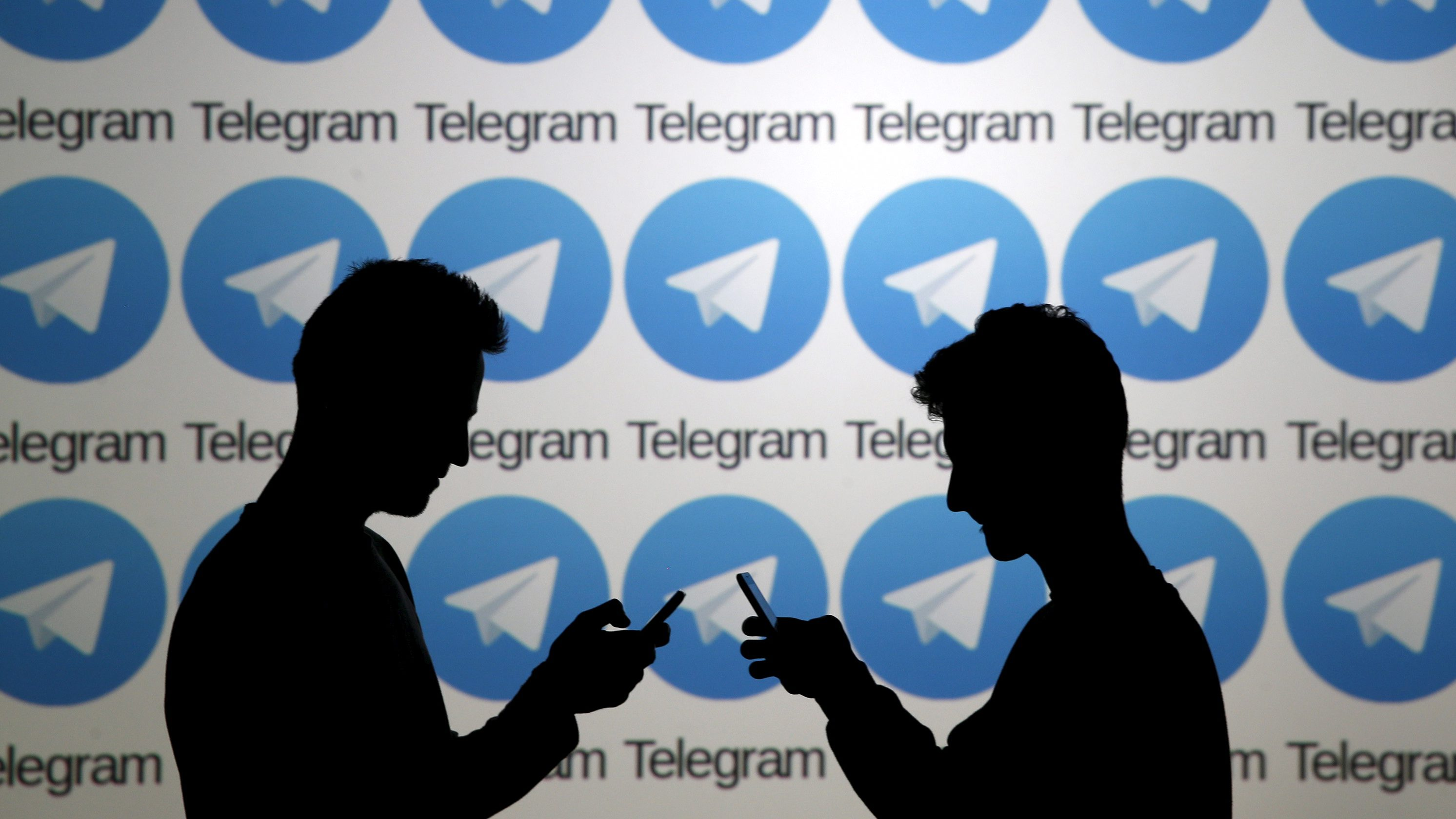 Two men pose with smartphones in front of a screen showing the Telegram logos in this picture illustration taken in Zenica, Bosnia and Herzegovina November 18, 2015. The mobile messaging service Telegram, created by the exiled founder of Russia's most popular social network site, has emerged as an important new promotional and recruitment platform for Islamic State. The service, set up two years ago, has caught on in many corners of the globe as an ultra-secure way to quickly upload and share videos, texts and voice messages. It counts 60 million active users around the world. Picture taken November 18.