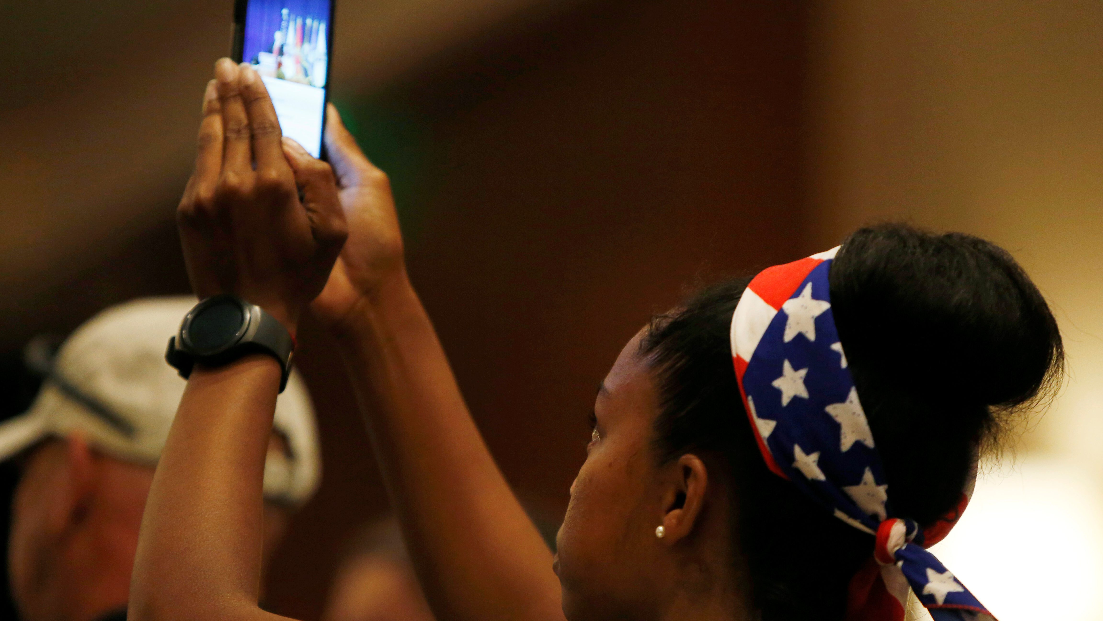 A young girl takes a photo of presumptive Republican presidential nominee Donald Trump (not pictured) during a speech in Virginia Beach, Virginia U.S. July 11, 2016.  REUTERS/Gary Cameron - S1AETOZYPLAA