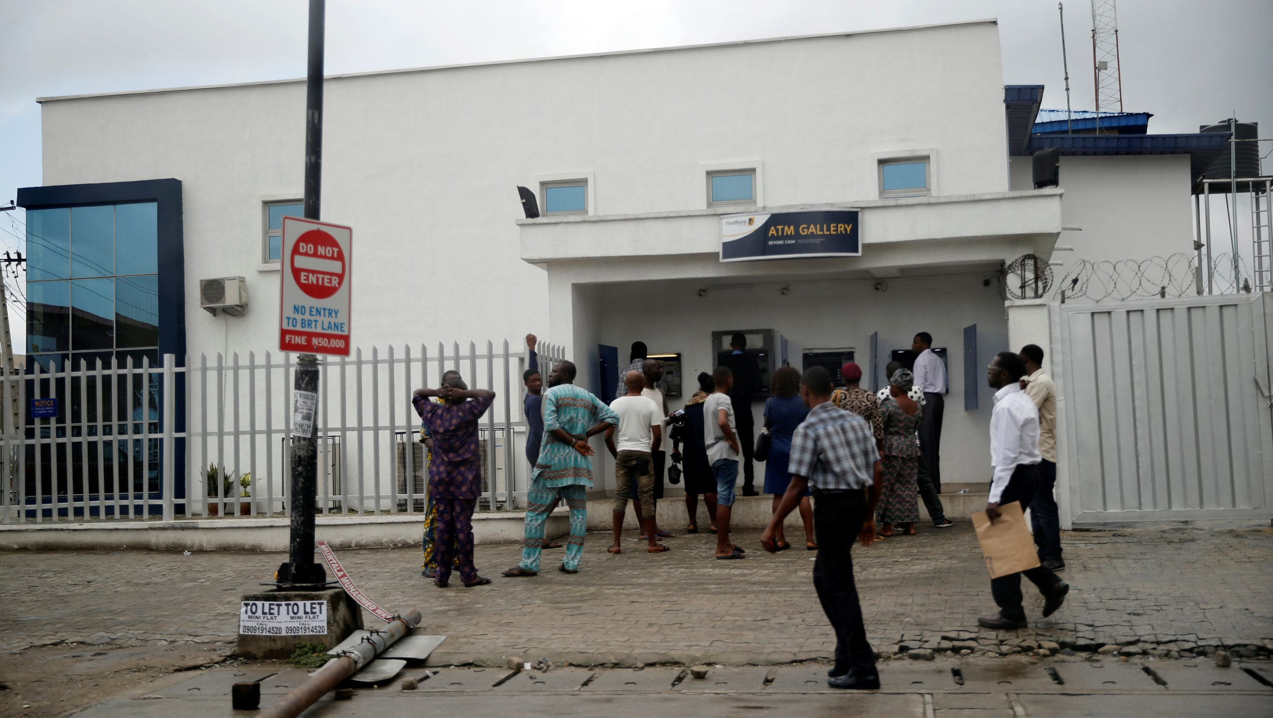 People queue to use the automated teller machine (ATM) in front of First bank along a road in Apapa district in Lagos