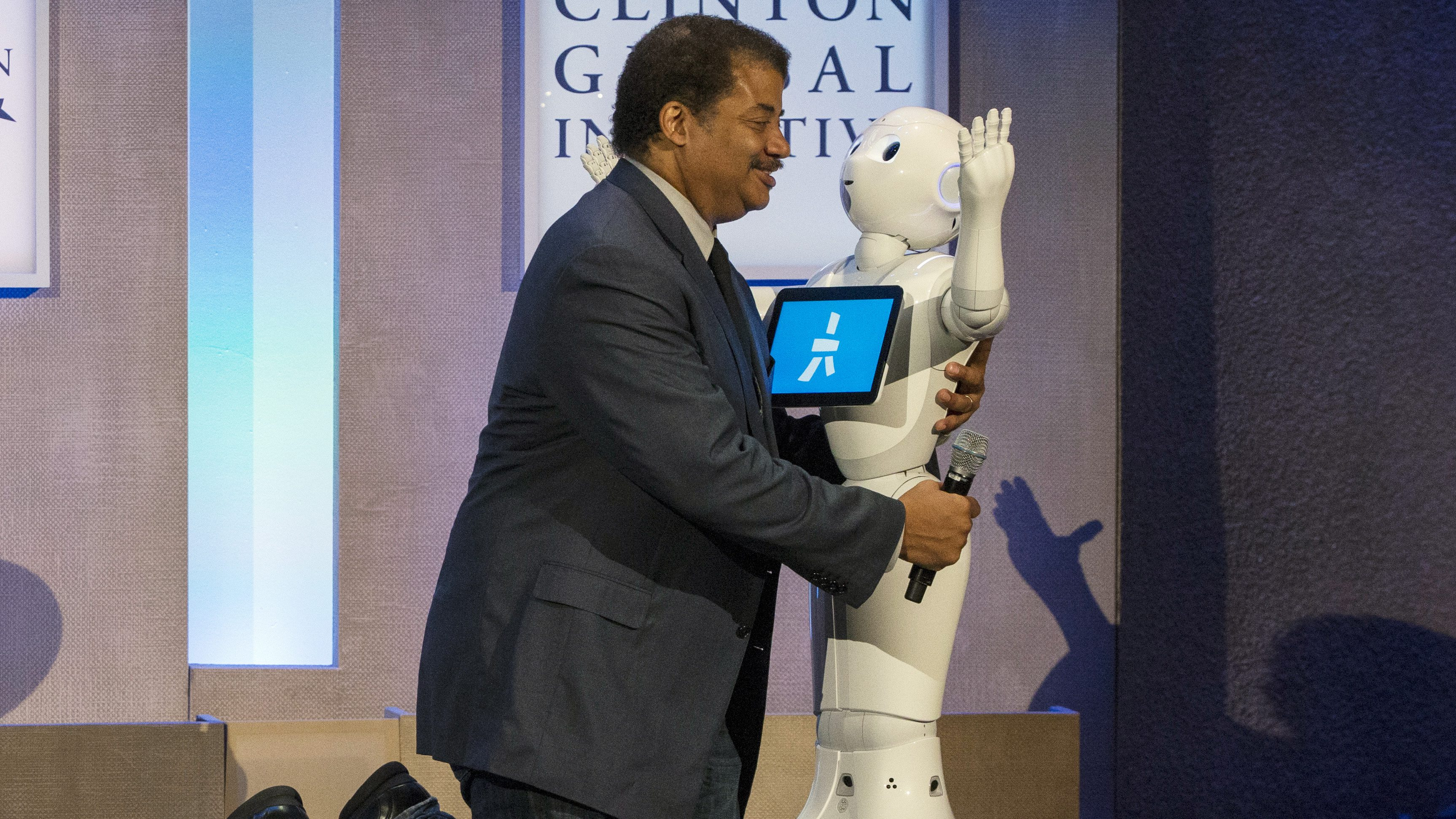 Astrophysicist Neil deGrasse Tyson greets Pepper, a social humanoid robot developed by Aldebaran for SoftBank, on stage during the Clinton Global Initiative's annual meeting in New York, September 28, 2015.  REUTERS/Brendan McDermid       TPX IMAGES OF THE DAY      - GF10000225493