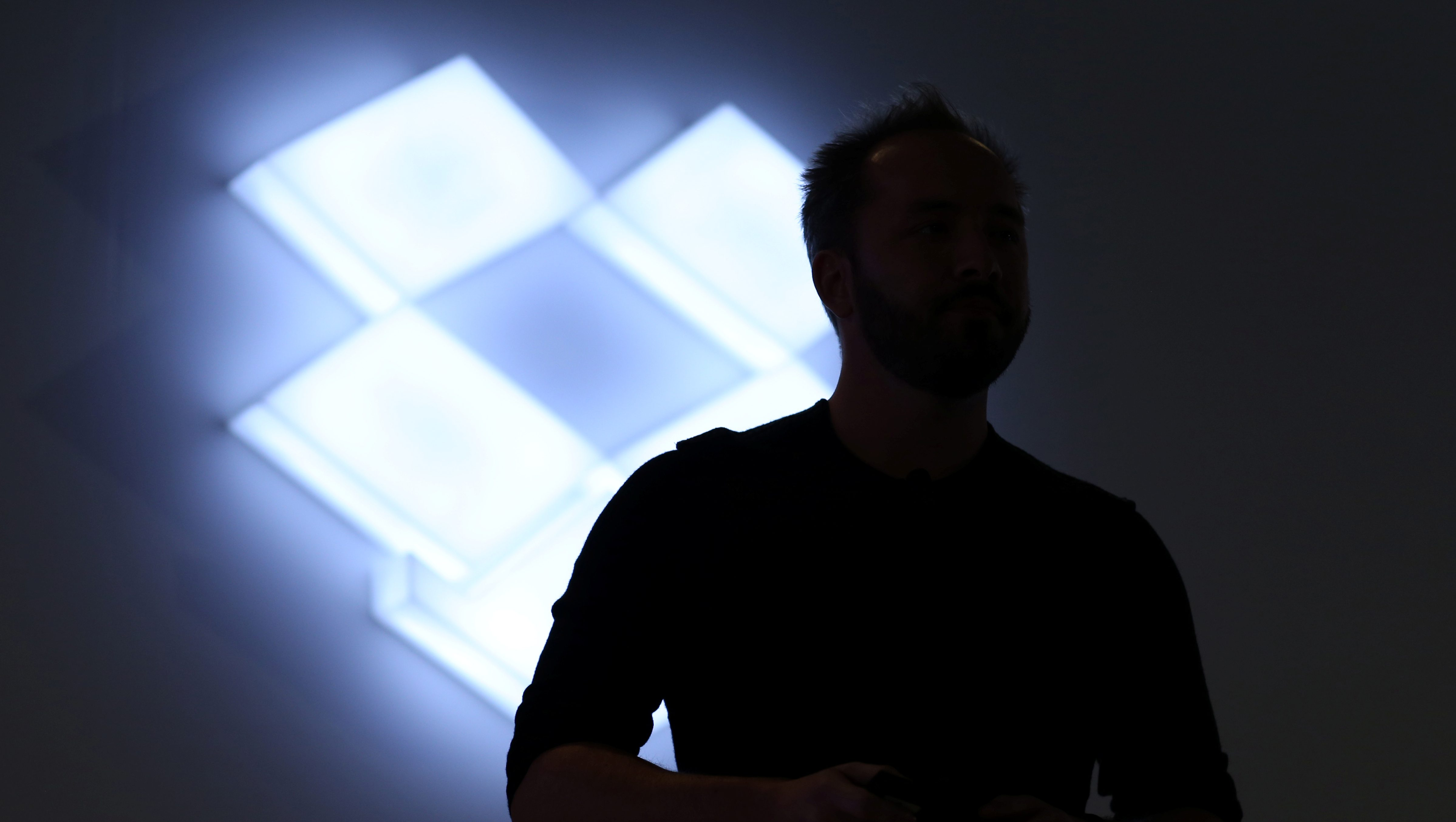 Drew Houston, Chief Executive Officer and founder of Dropbox, stands in front of the company's logo at an announcement event in San Francisco, California, U.S., January 30, 2017. REUTERS/Beck Diefenbach - RC12885F1140