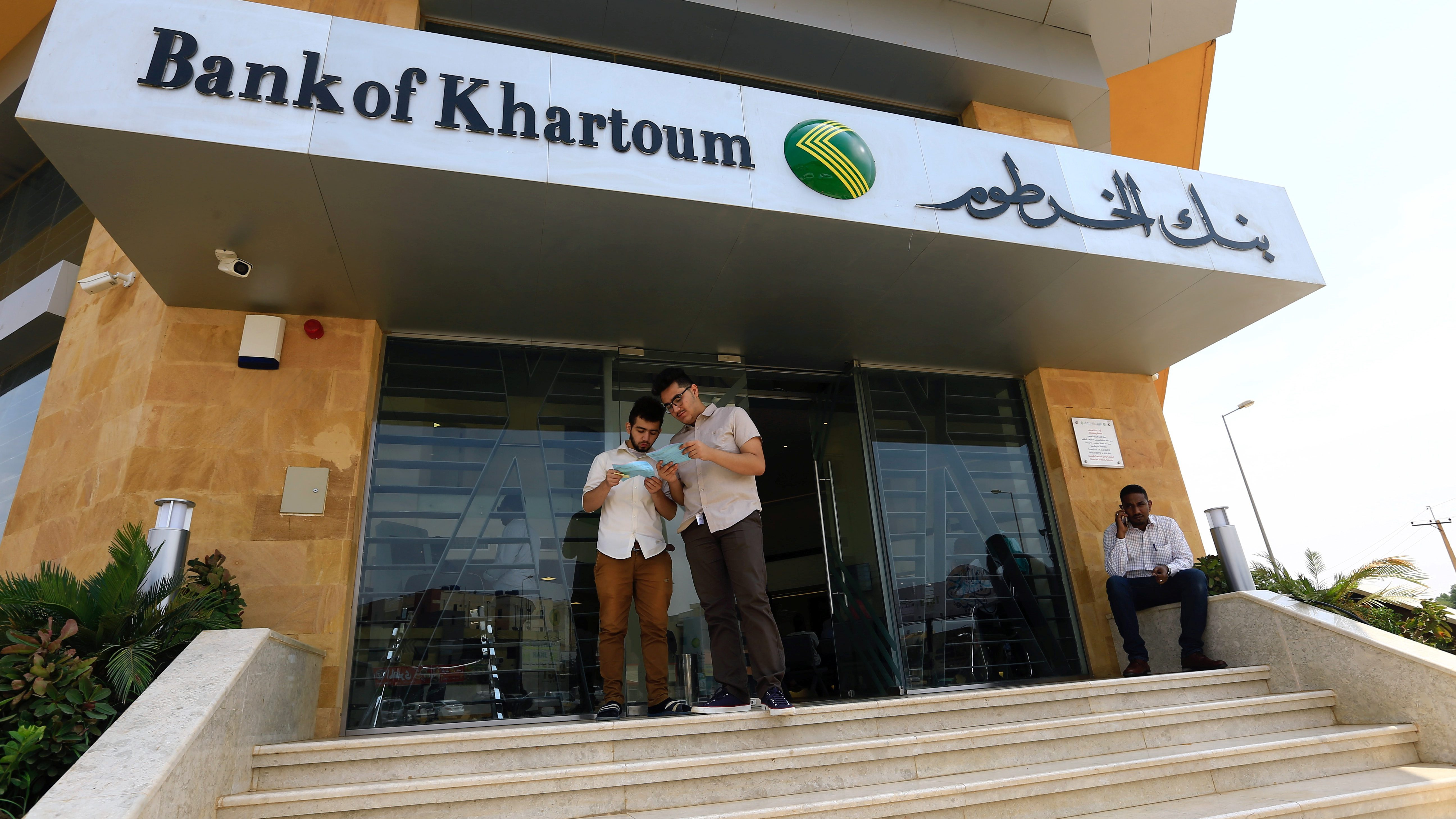 Customers wait outside the Bank of Khartoum, in Khartoum
