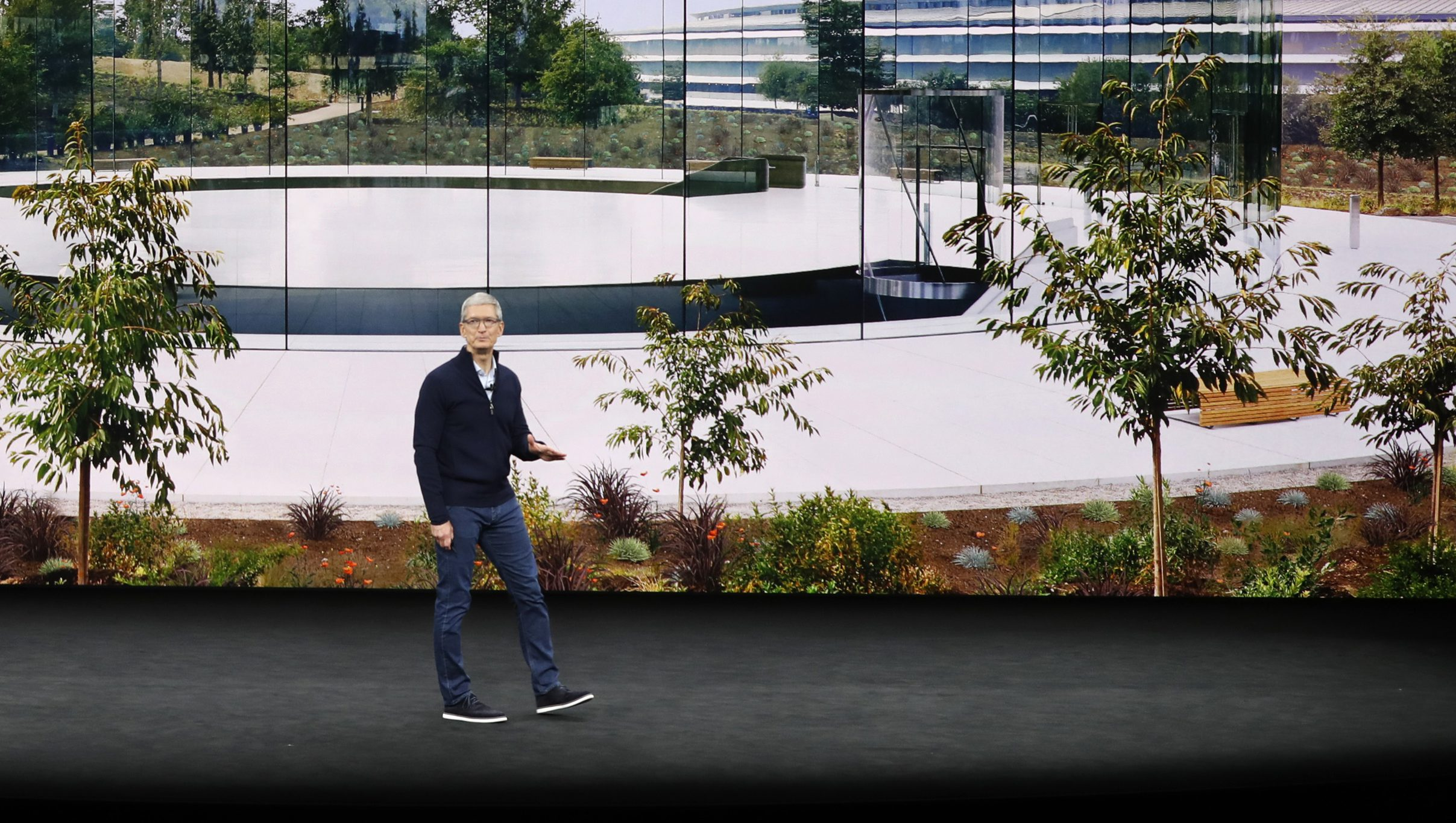 Tim Cook on stage in front of a photo of Apple Campus