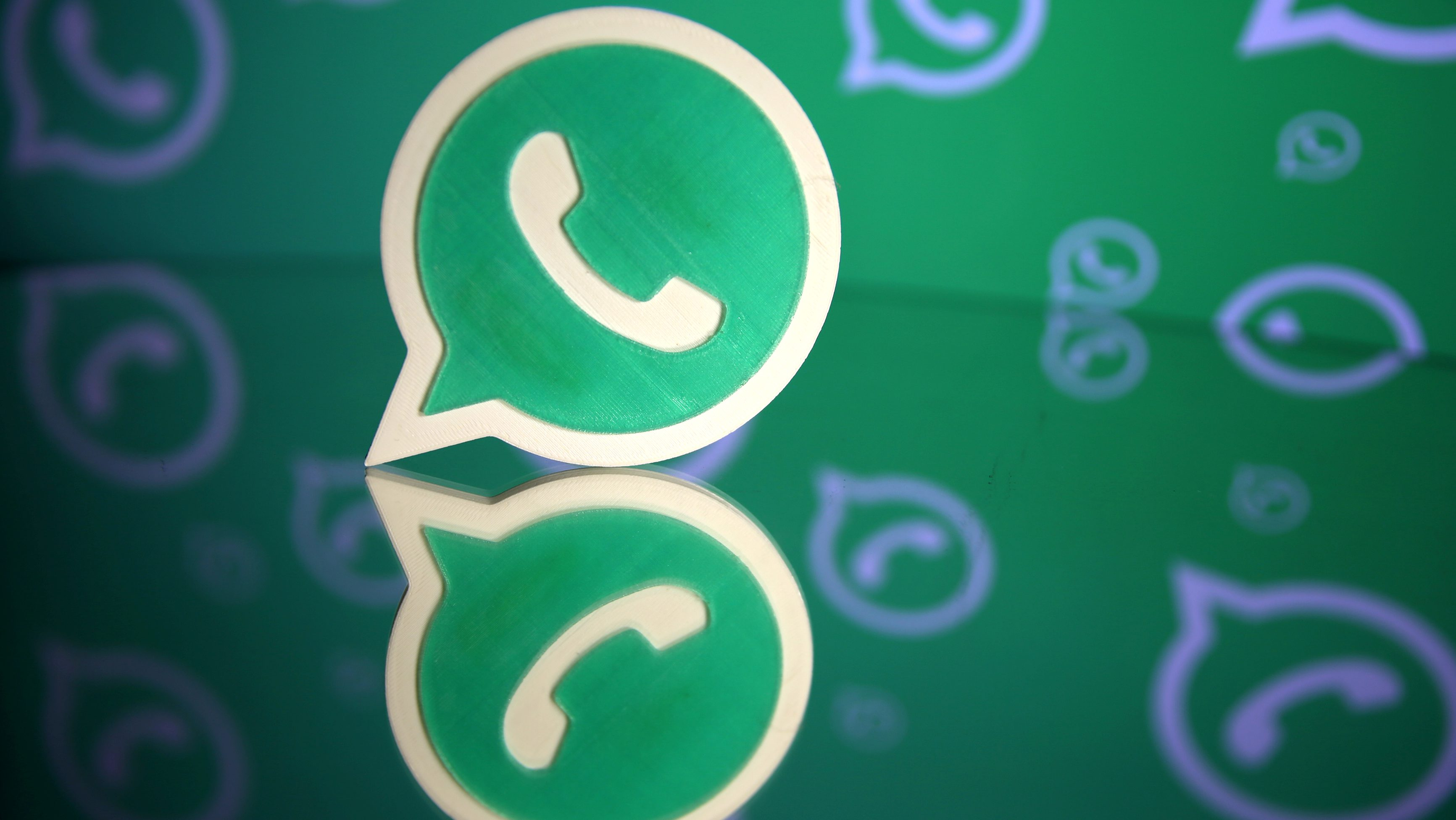 A 3D printed Whatsapp logo is seen in front of a displayed Whatsapp logo in this illustration
