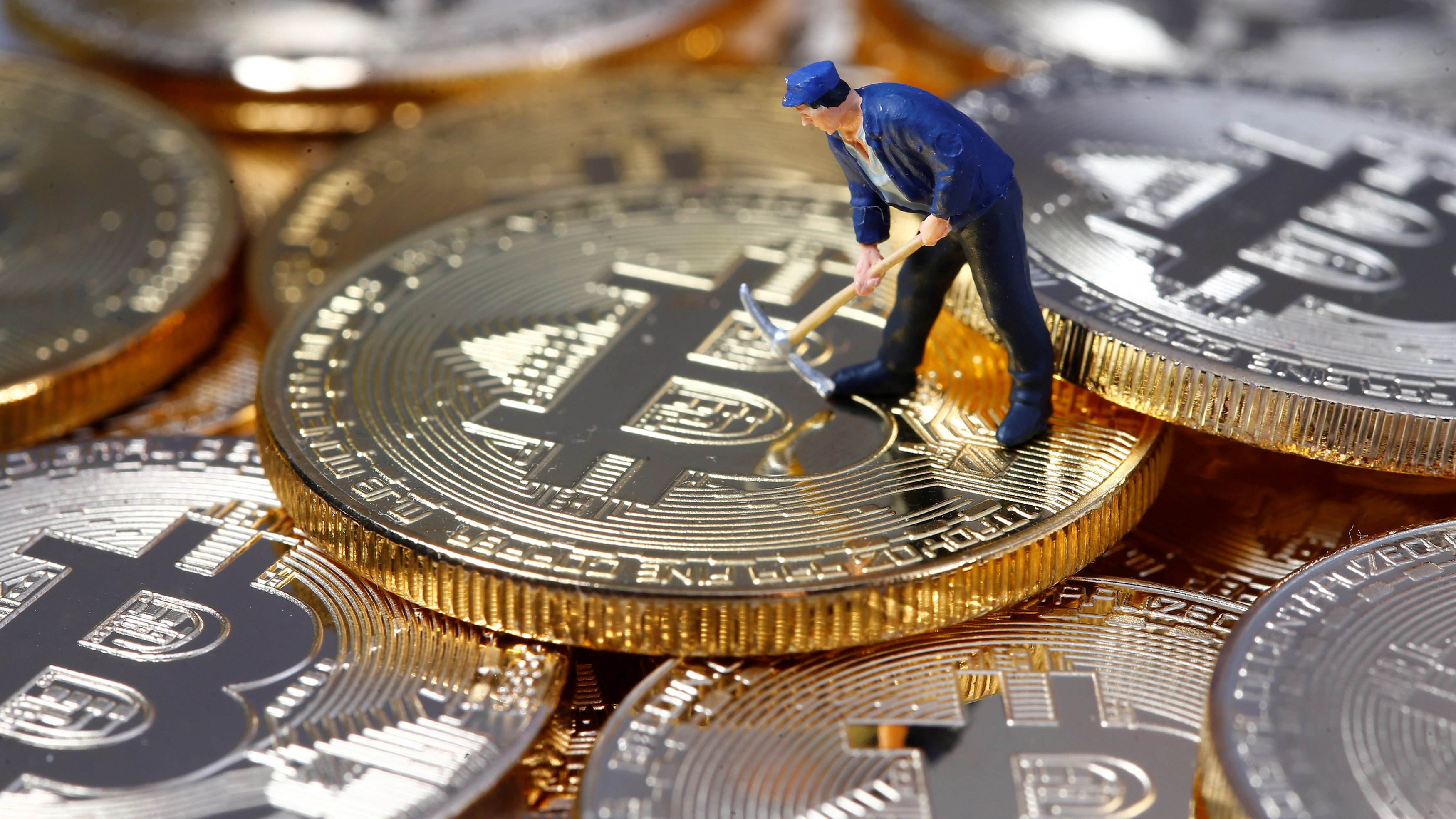 A small toy figure is seen on representations of the Bitcoin virtual currency in this illustration picture, December 26, 2017. REUTERS/Dado Ruvic/Illustration - RC1749BEB4F0