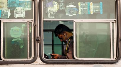 A man looks into his phone as he travels in an intercity bus service in New Delhi