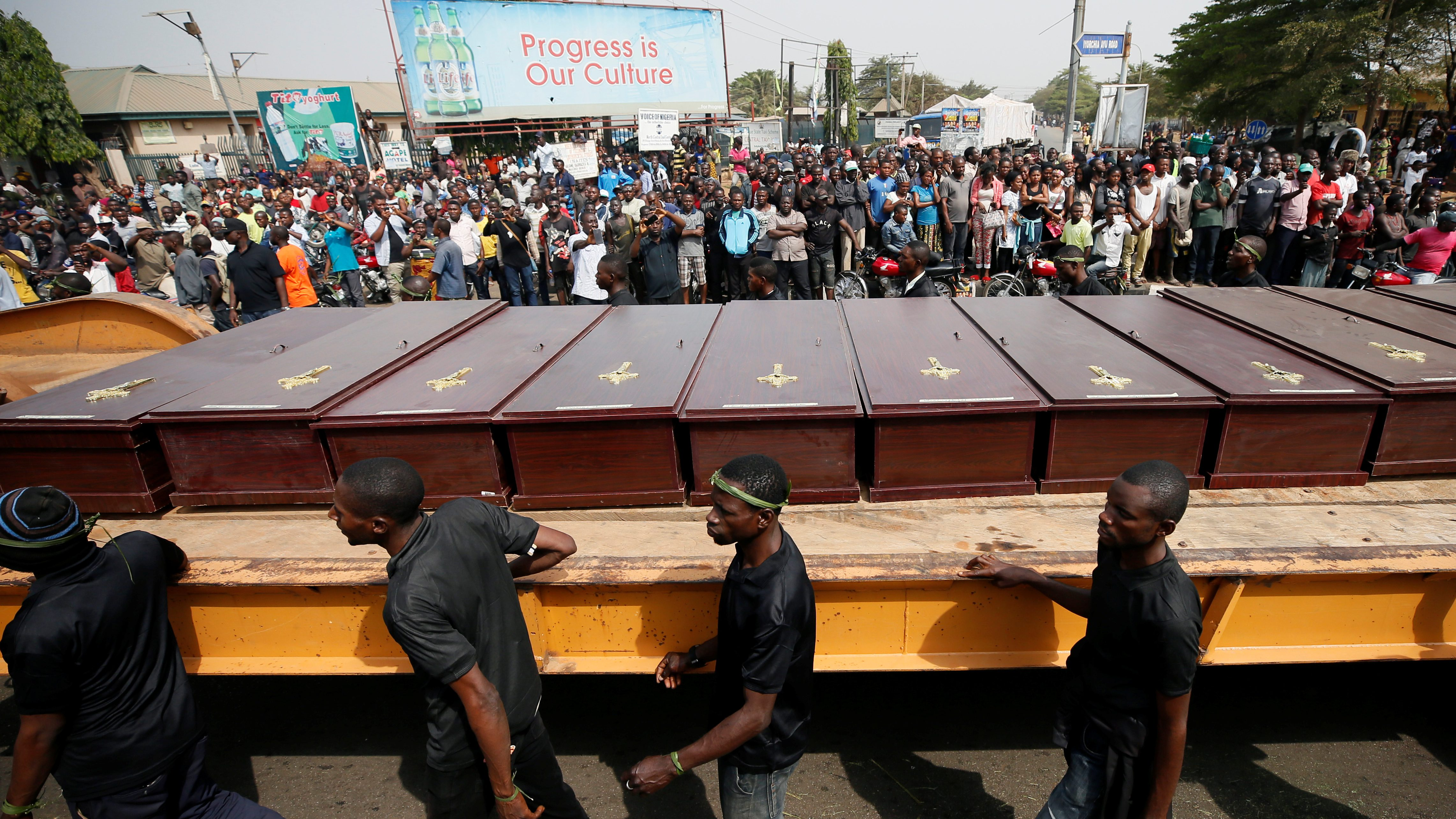 Men march along the truck carrying the coffins of people killed by the Fulani herdsmen, in Makurdi