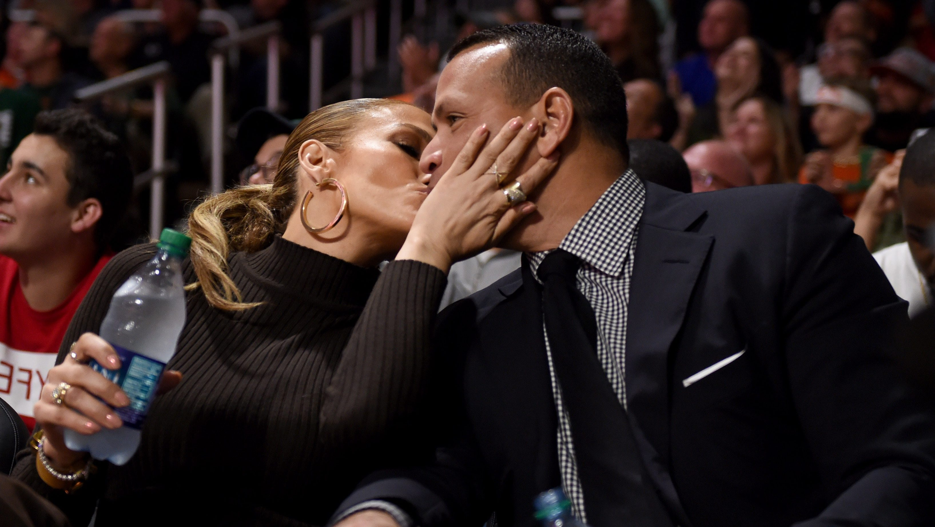Recording artist Jennifer Lopez and former New York Yankees baseball player Alex Rodriguez kiss during an NCAA basketball game between the Miami Hurricanes and the Duke Blue Devils at Watsco Center.