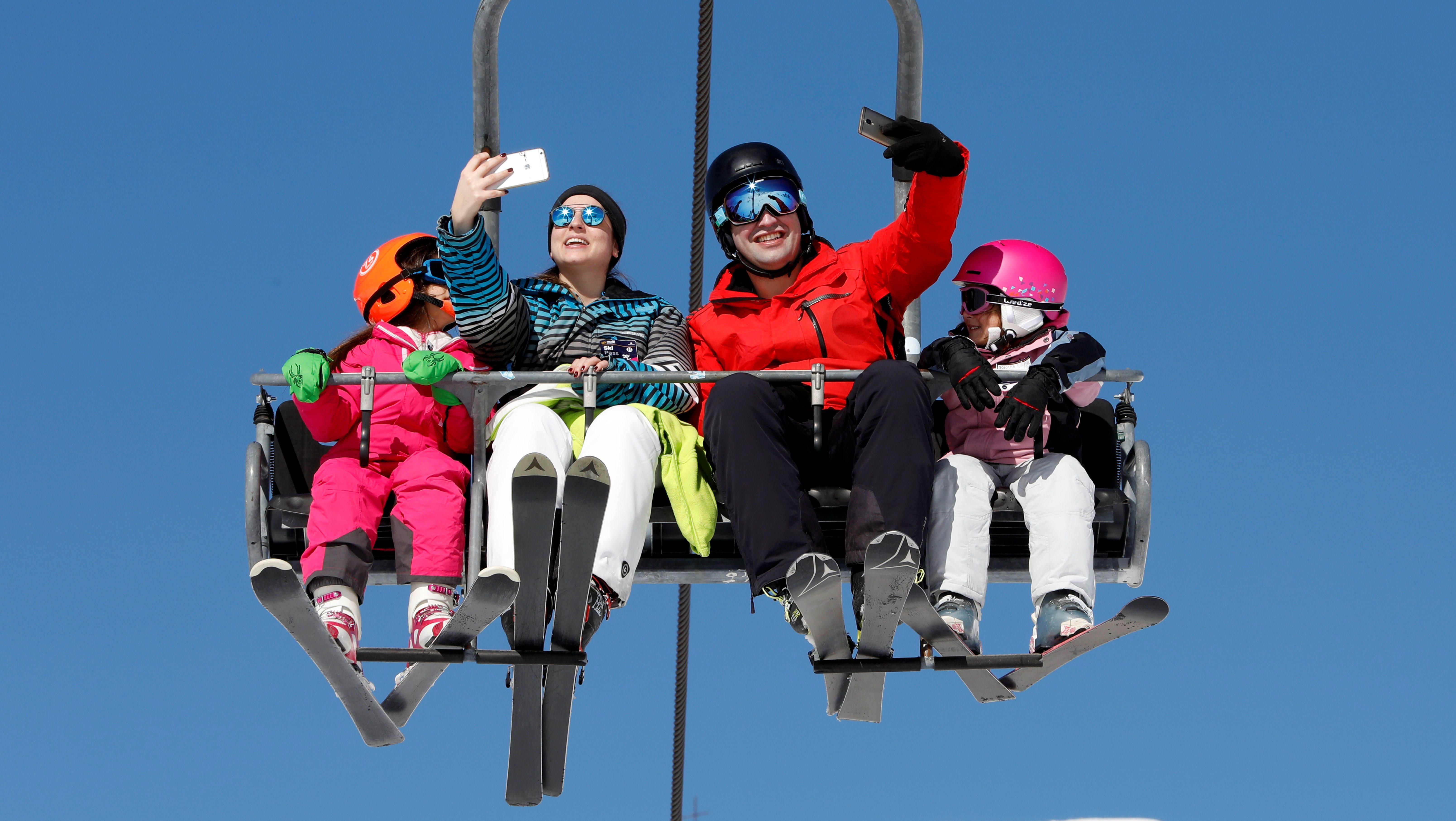 A couple takes selfies as they ride a ski lift at the Mzaar Ski Resort in Kfardebian, Lebanon January 20, 2018. REUTERS/Jamal Saidi - RC160A11D500