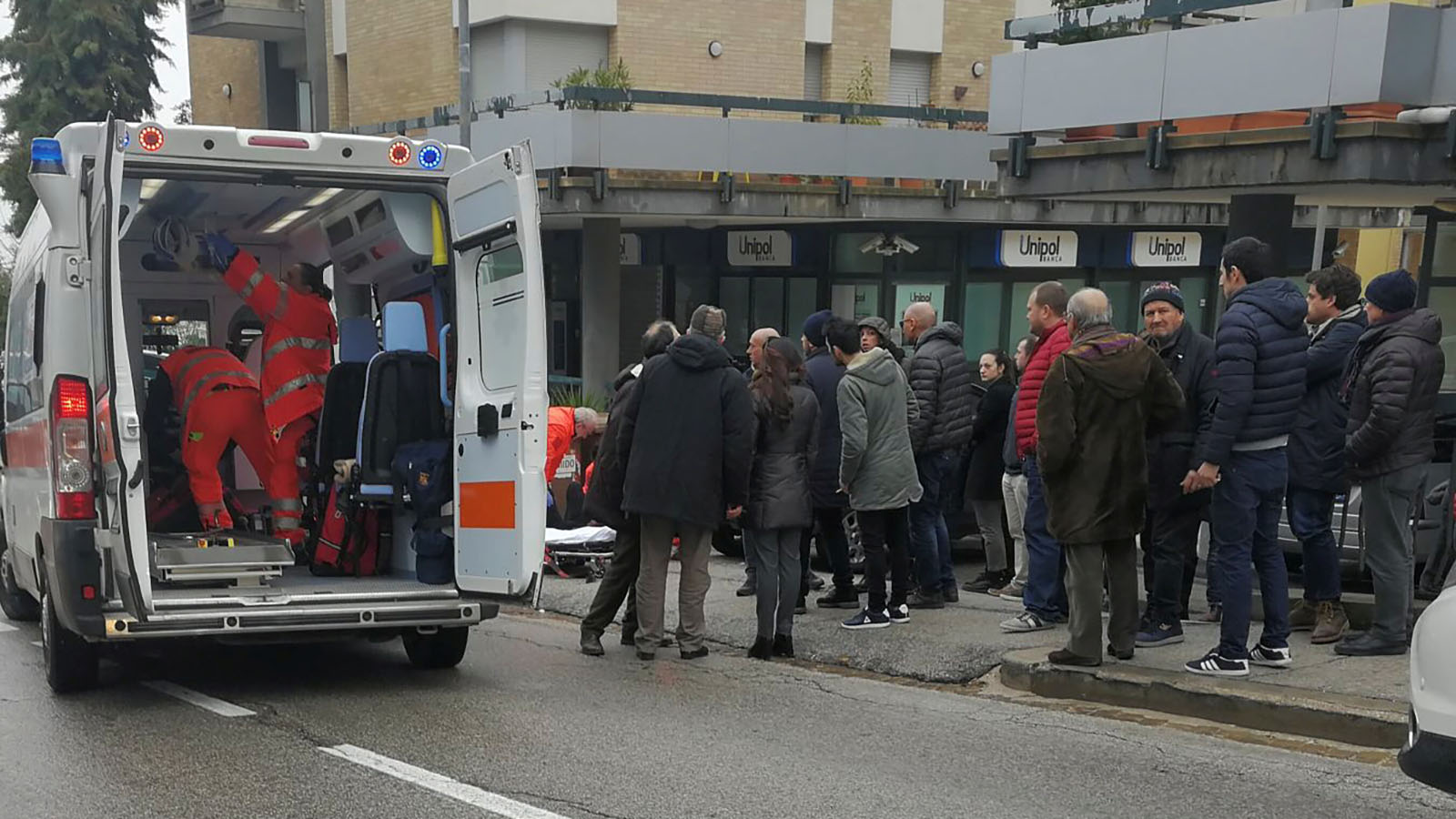 People look at healthcare personnel taking care of an injured person after being shot by gunfire from a vehicle, in Macerata