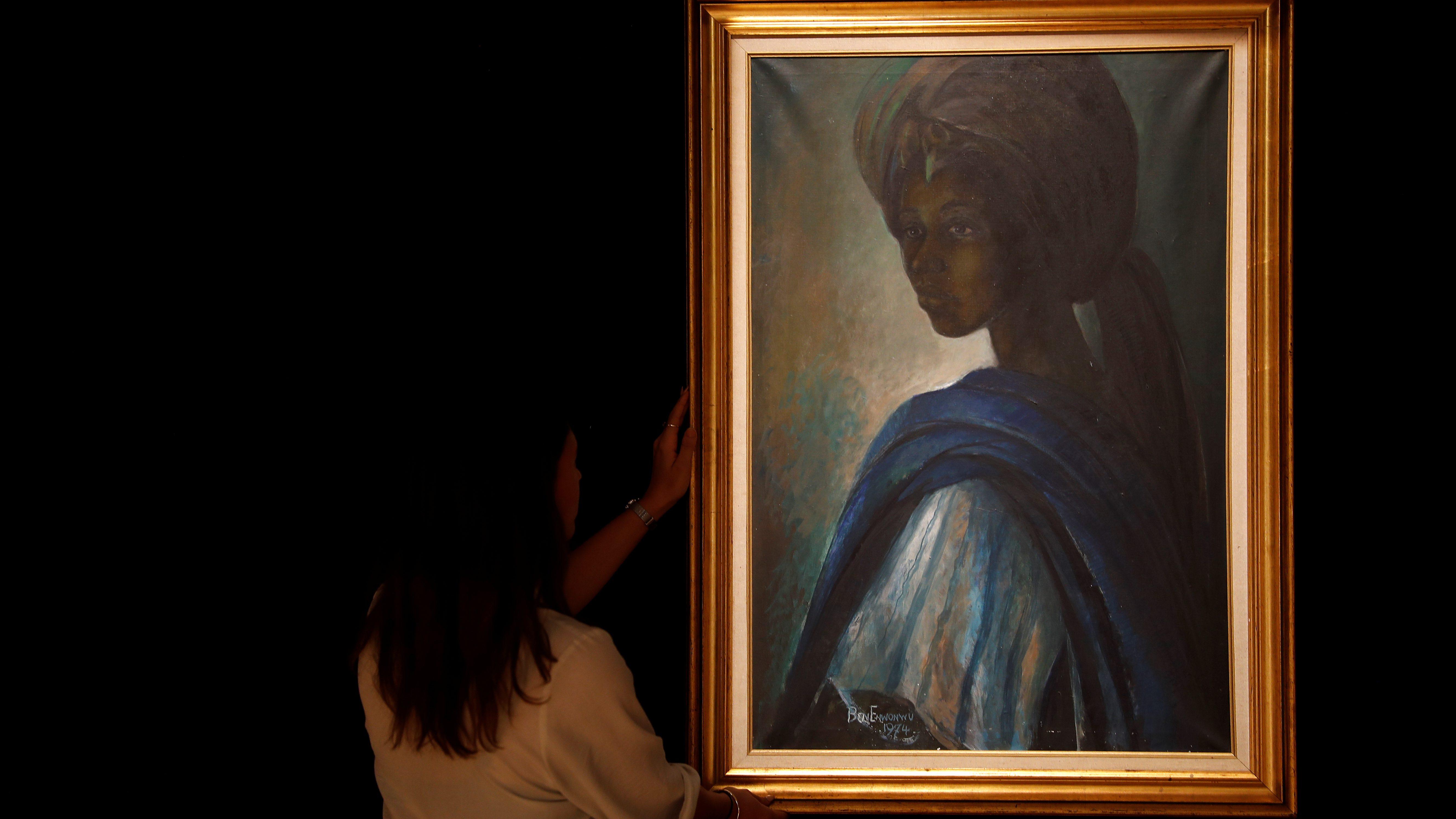 "A worker at Bonhams auctioneers poses next to Tutu,"" by Nigeria's best-known modern artist Ben Enwonwu, ahead of its sale, in London"