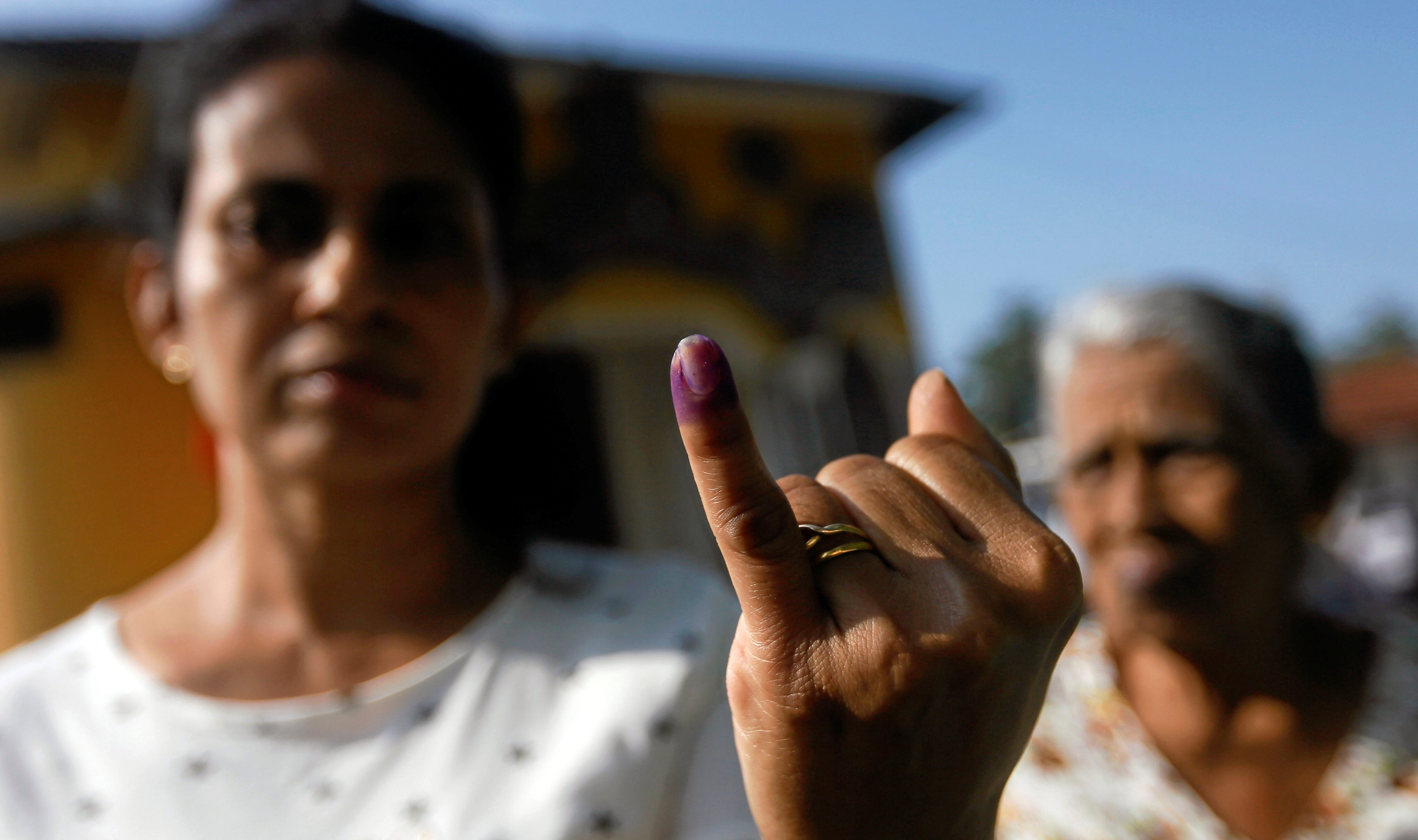 A woman shows her ink-stained finger after casting her vote at a polling station during the long-delayed local government elections in Colombo, Sri Lanka February 10, 2018.