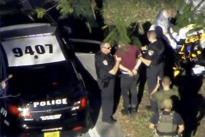 A man placed in handcuffs is led by police near Marjory Stoneman Douglas High School.