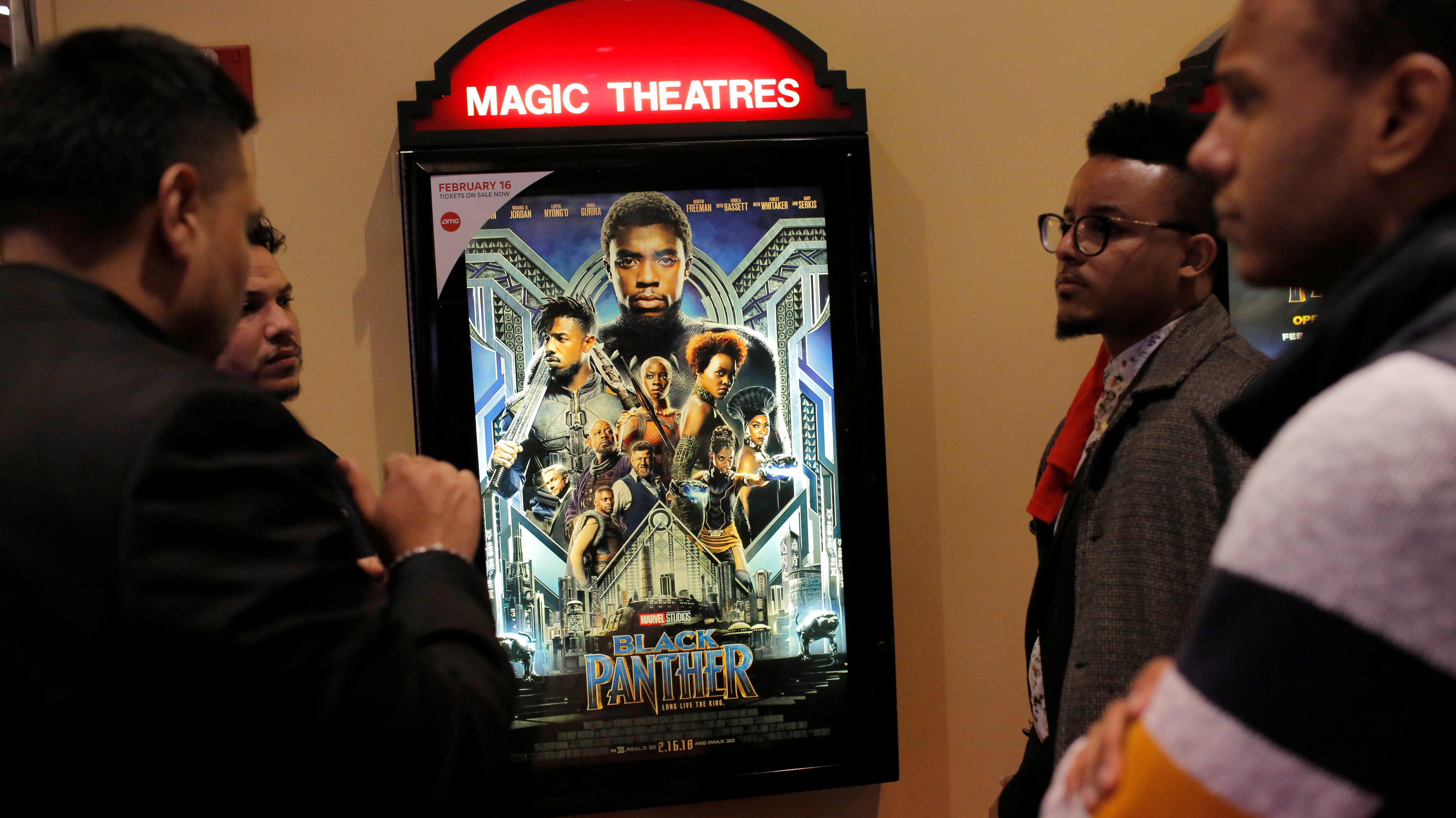 """A group of men gather in front of a poster advertising the film """"Black Panther"""" on its opening night of screenings at the AMC Magic Johnson Harlem 9 cinemas in Manhattan, New York, U.S., February 15, 2018.  REUTERS/Andrew Kelly - RC156691BC20"""