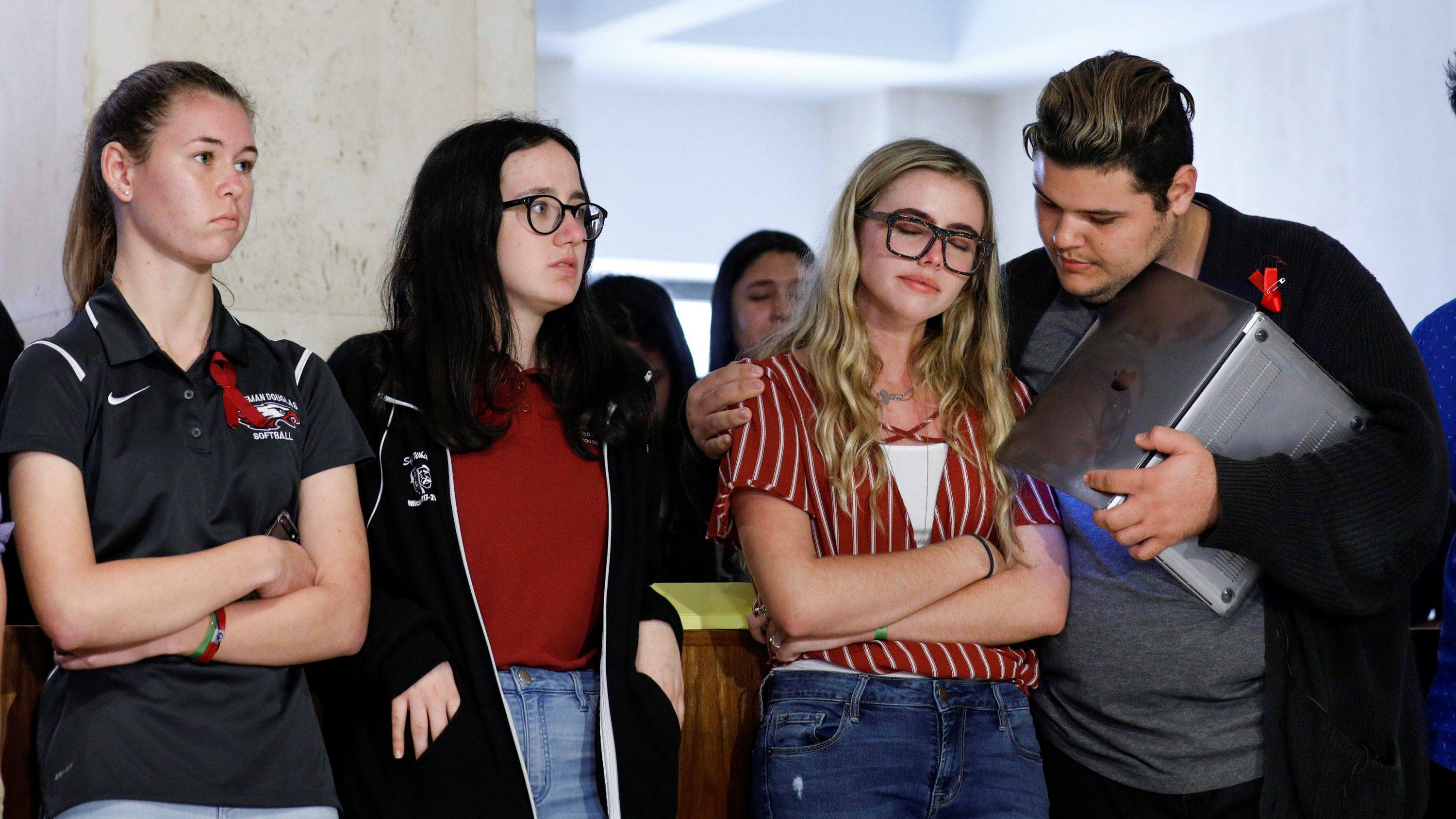 Delaney Tarr (3rd left) is consoled by fellow Marjory Stoneman Douglas High School student Dimitri Hoth (R) while Sarah Chadwick (L) and Sophie Whitney join them to listen to other survivors of last week's mass shooting on their campus during a news conference, in Tallahassee, Florida, U.S., February 21, 2018.