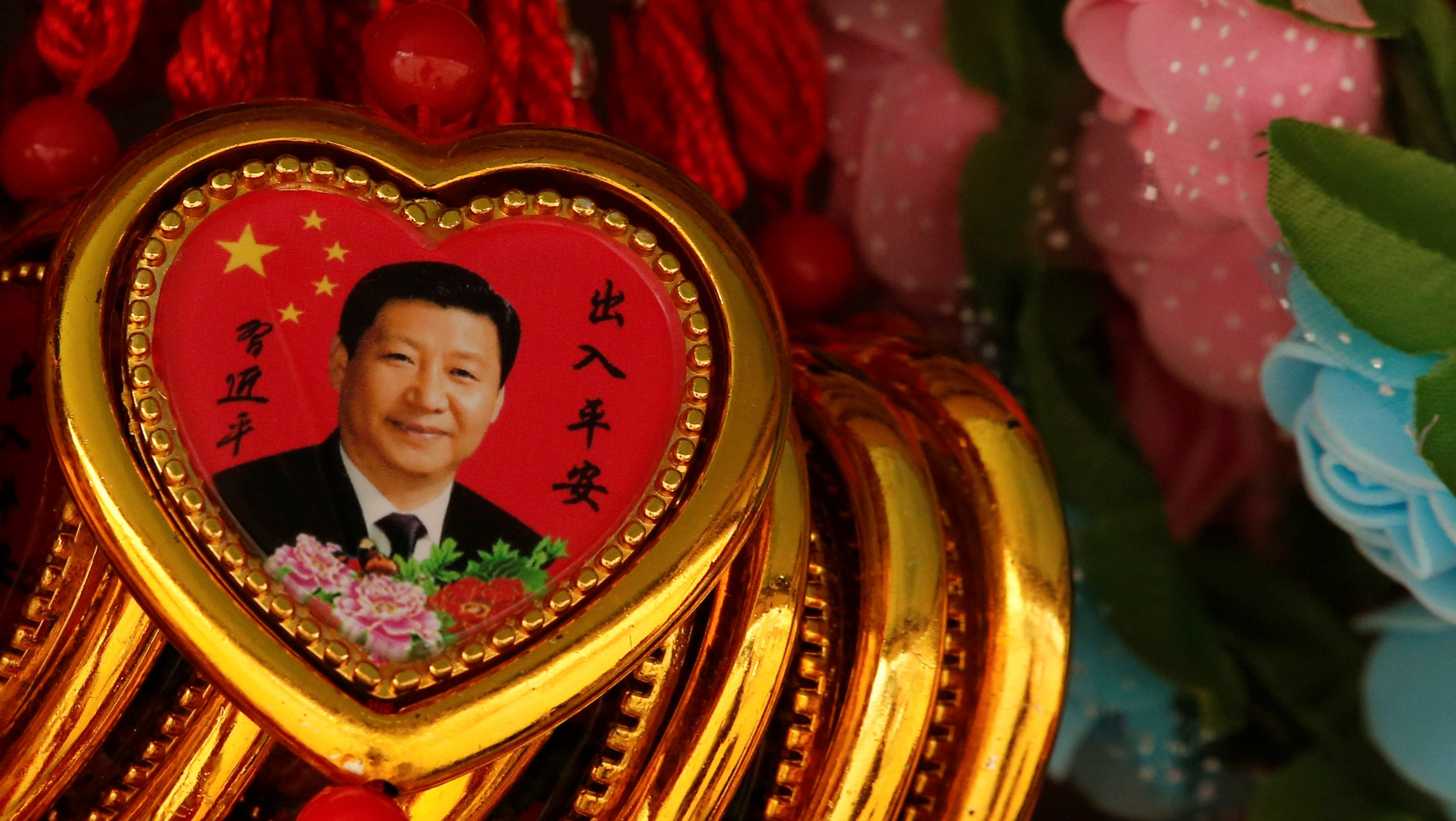 FILE PHOTO: Souvenir necklaces with a portrait of Chinese President Xi Jinping are displayed for sale at a stall in Tiananmen Square in Beijing, China, February 26, 2018.