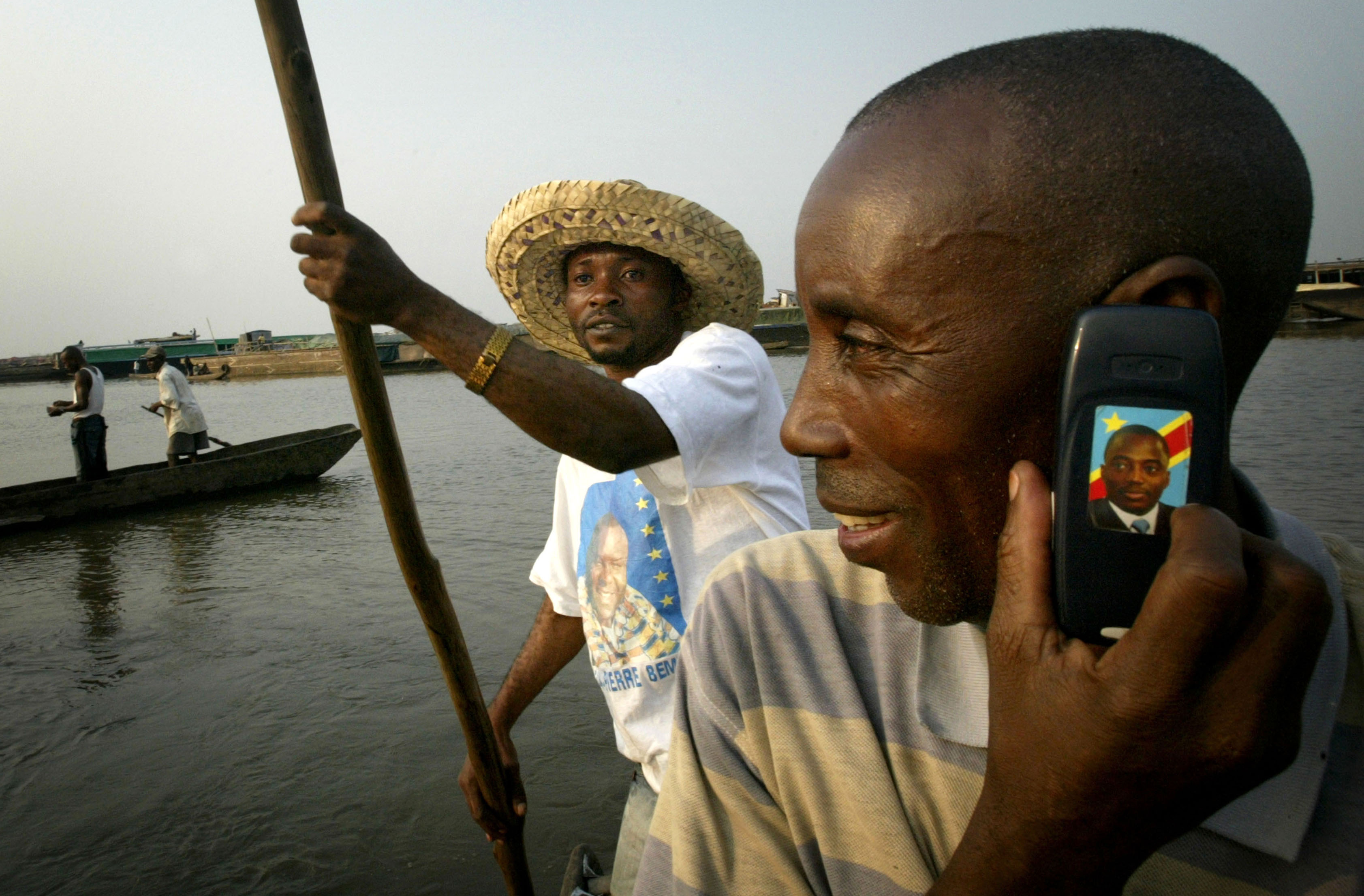 A man uses a mobile phone bearing the likeness of [President Joseph Kabila], while the oarsman wears a T-shirt showing opposition candidate [Jean-Pierre Bemba], on the Congo river near the capital Kinshasa, July 23, 2006. [Powerful Catholic leaders in Congo's capital urged voters on Sunday to boycott historic elections next week unless allegations of fraud were addressed, raising concerns over the first multi-party polls in 40 years.] - PBEAHUNKOER