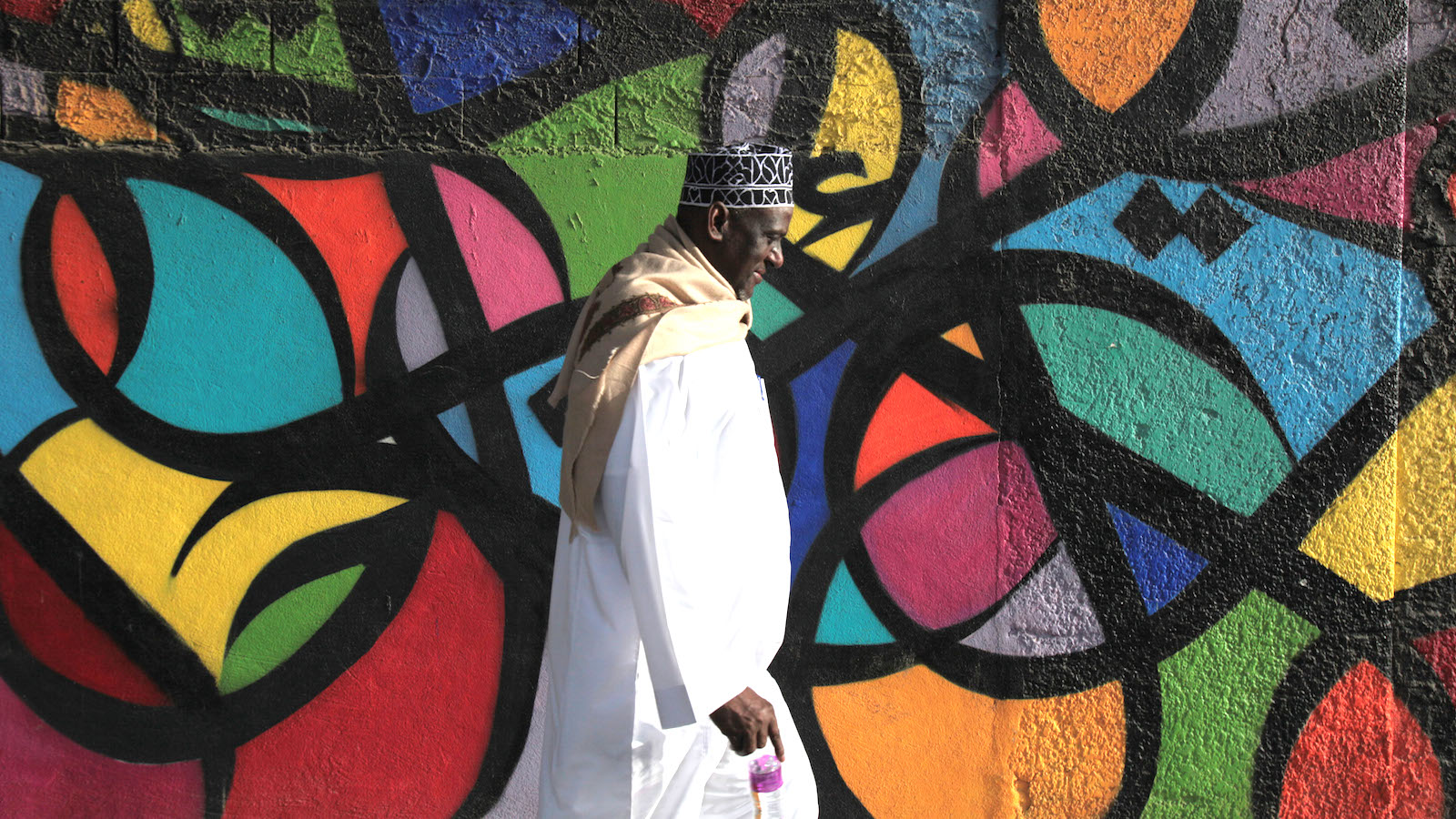 A man walks by a graffiti on a wall in the old city of Jeddah, Saudi Arabia, Friday, May 9, 2014. Jeddah has been a traditional hub for commerce along the Red Sea and the port of entry for many Muslims traveling to Mecca to perform the religious obligations for the Hajj pilgrimage. Many Arab and African pilgrims years ago stayed in Jeddah, never returning to their home countries and many eventually melted into Saudi society. (AP Photo/Hasan Jamali)