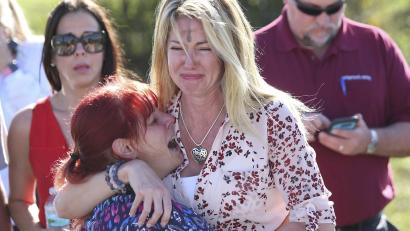 Parents wait for news after a reports of a school shooting in parkland, fla.