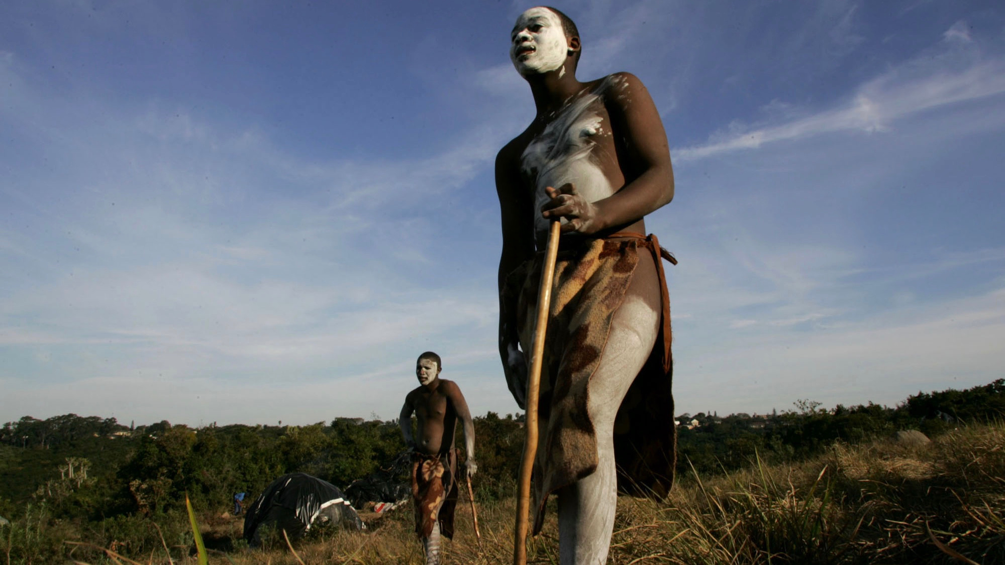 Young unidentified initiates, with their faces and parts of their bodies caked in white lime clay, and blankets used as loin cloths, during their rite of transformation from boy to manhood near Port St, John's, South Africa, Saturday July 8,  2006. During the process boys, often under age, leave their family homes to fend for themselves, with fellow initiates, during which time they are circumsised and face the elements of nature. The huts in the background are covered in heavy black plastic to ward off the winter night cold as they take part in the in the tribal Xhosa tradition.   (AP Photo/Obed Zilwa)
