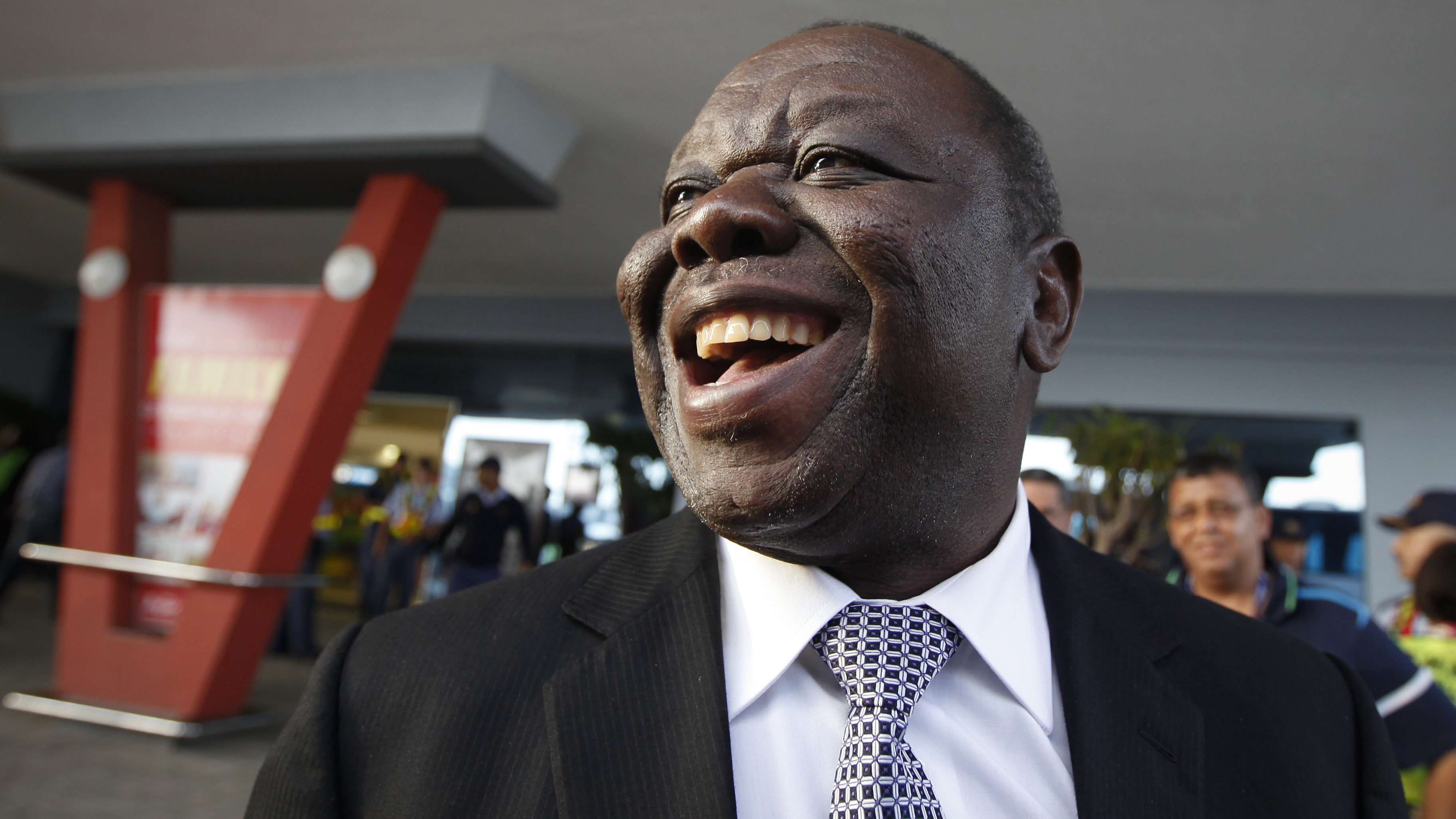 Prime Minister of Zimbabwe Morgan Tsvangirai stands outside the East London airport in Eastern Cape, South Africa, after after arriving to attend the late former South African President Nelson Mandela's funeral, Saturday, December 14, 2013. (AP Photo/Dai Kurokawa, Pool)