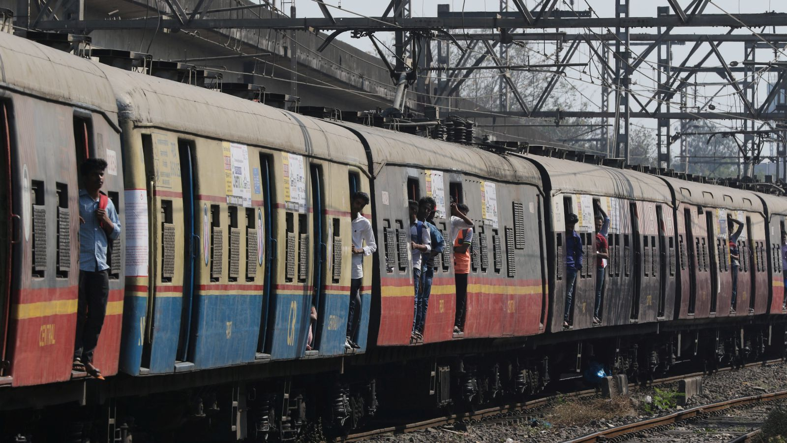 People travel on the foot board of a local train in Mumbai, India, February 1, 2017.