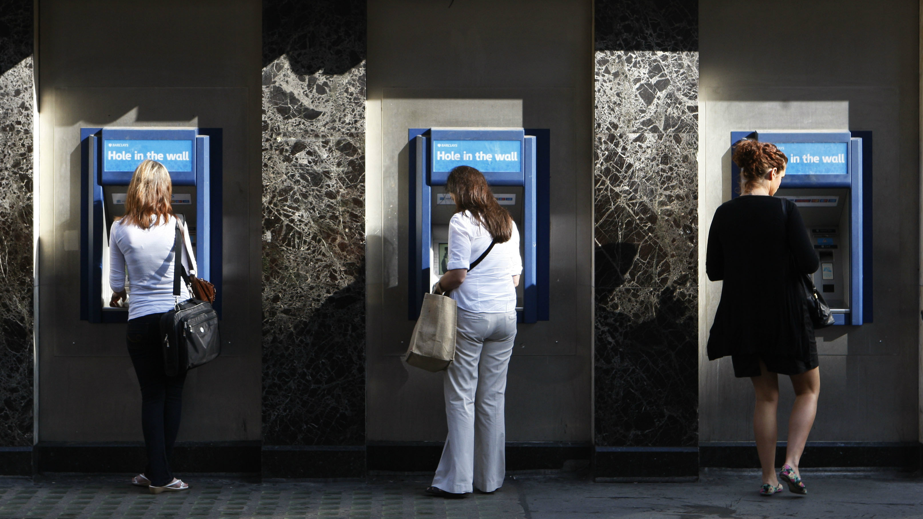 People use the cash machines at a branch of Barclays Bank in central London