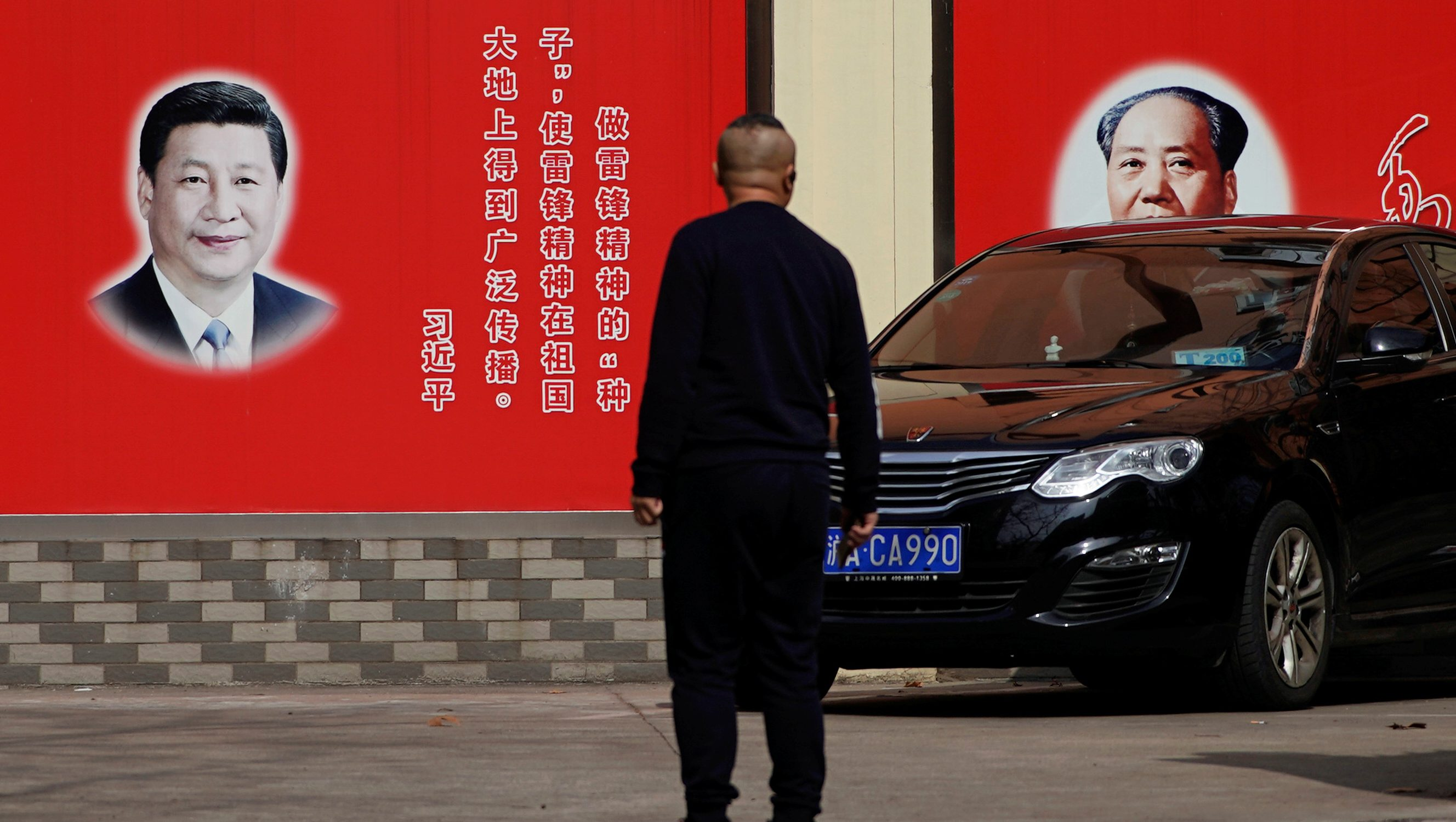 Pictures of Chinese President Xi Jinping and late Chinese Chairman Mao Zedong overlook a street in Shanghai, China February 26, 2018.