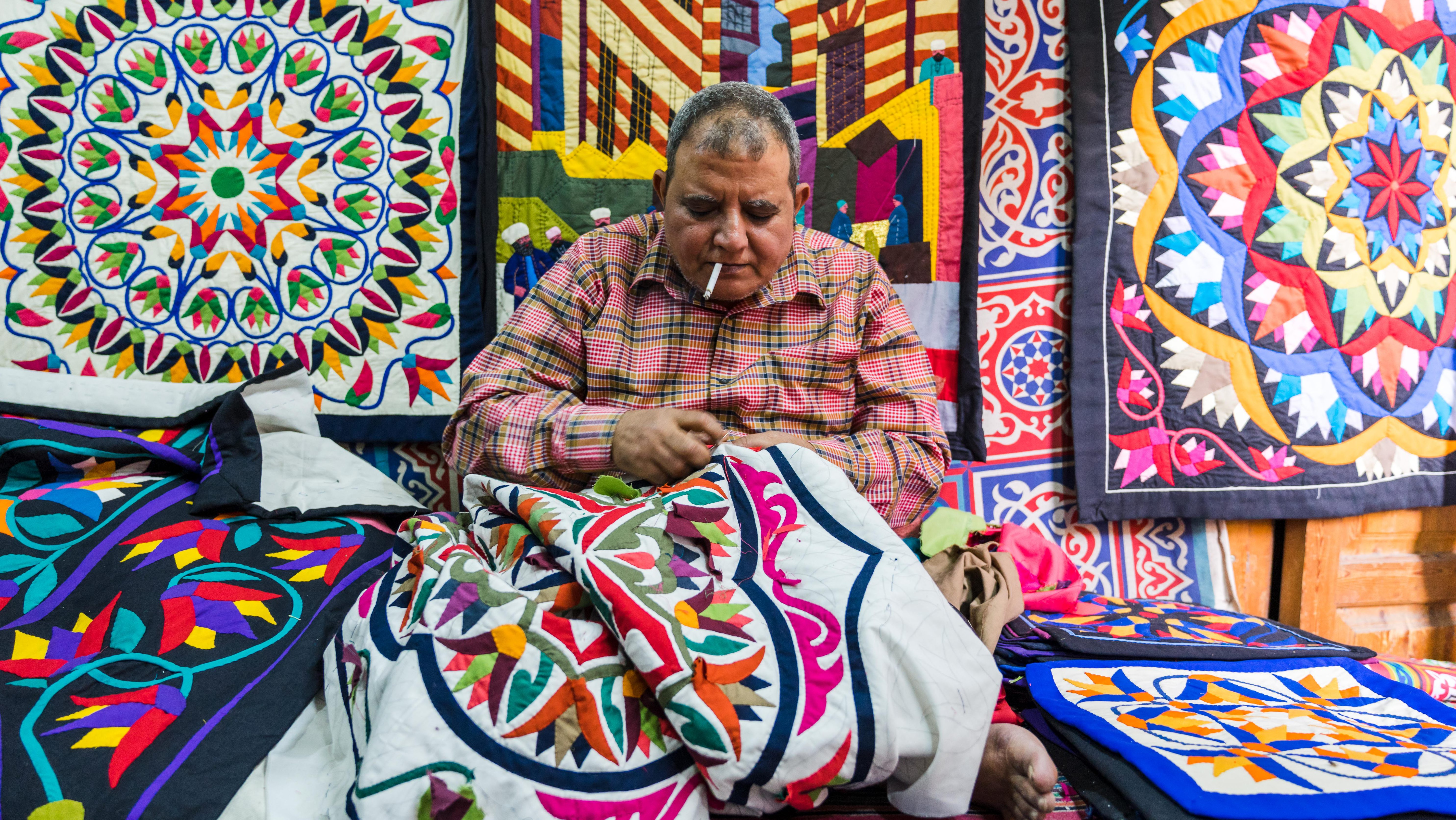 An artisan stitching a new design for a tent. For centuries Khayamiya artisans produced tents, cloths and saddles for those embarking on hajj, the pilgrimage to Mecca. The Sultan, sitting nearby on the ancient Fatimid gate, Bab Zuwaila, would watch the caravan depart in procession.