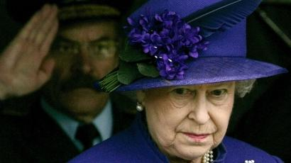 Queen Elizabeth wears a purple suit and matching hat.