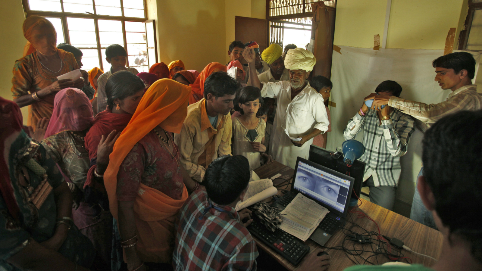 Villagers crowd inside an enrolment centre for the Unique Identification (UID) database system at Merta district in the desert Indian state of Rajasthan February 21, 2013. In a more ambitious version of programmes that have slashed poverty in Brazil and Mexico, the Indian government has begun to use the UID database, known as Aadhaar, to make direct cash transfers to the poor, in an attempt to cut out frauds who siphon billions of dollars from welfare schemes. Picture taken February 21, 2013.
