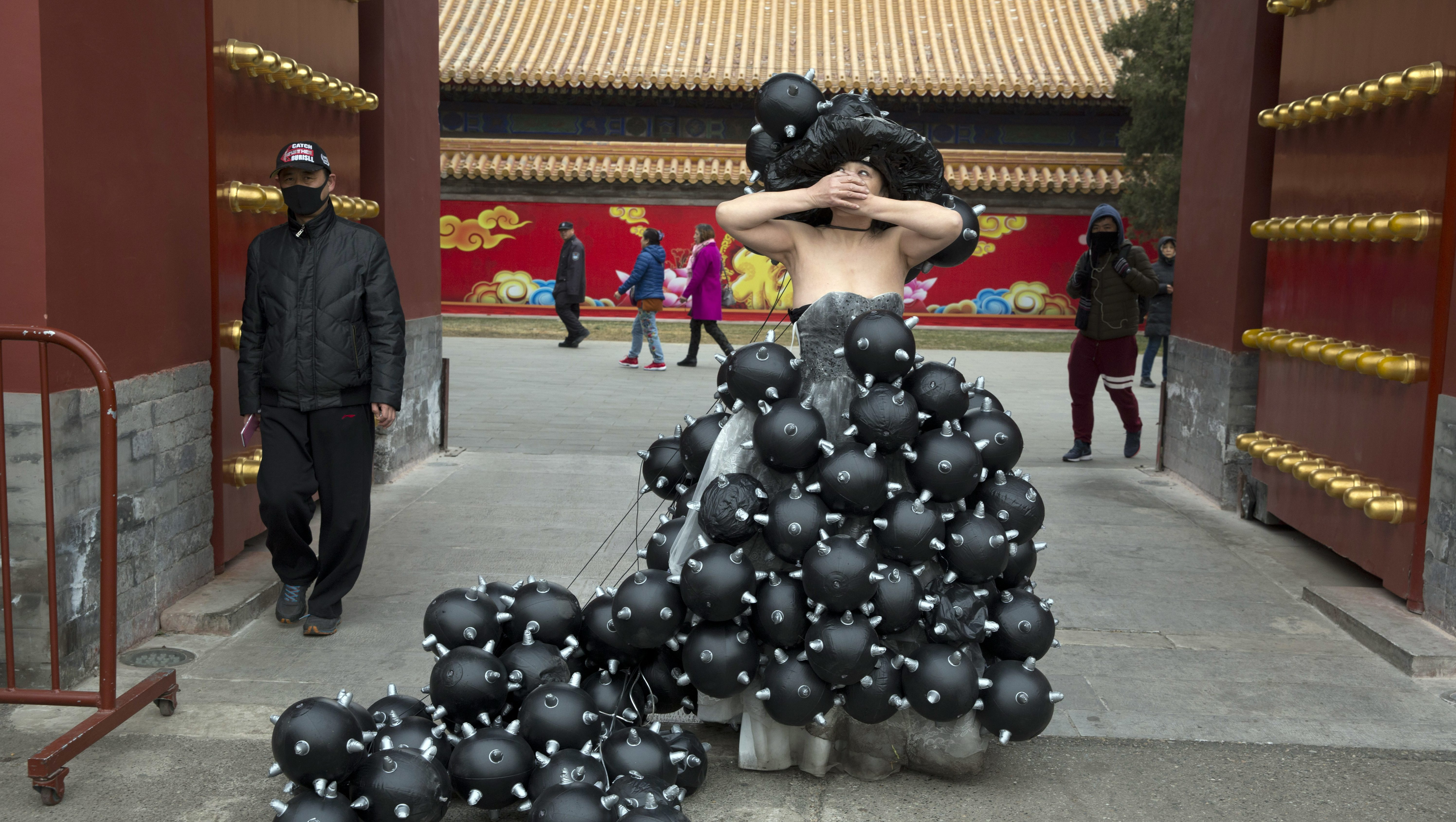 Performance artiste Kong Ning dresses in a gown depicting black granule during a street performance to raise awareness of air pollution in Beijing on Sunday, March 4, 2018. (AP Photo/Ng Han Guan)