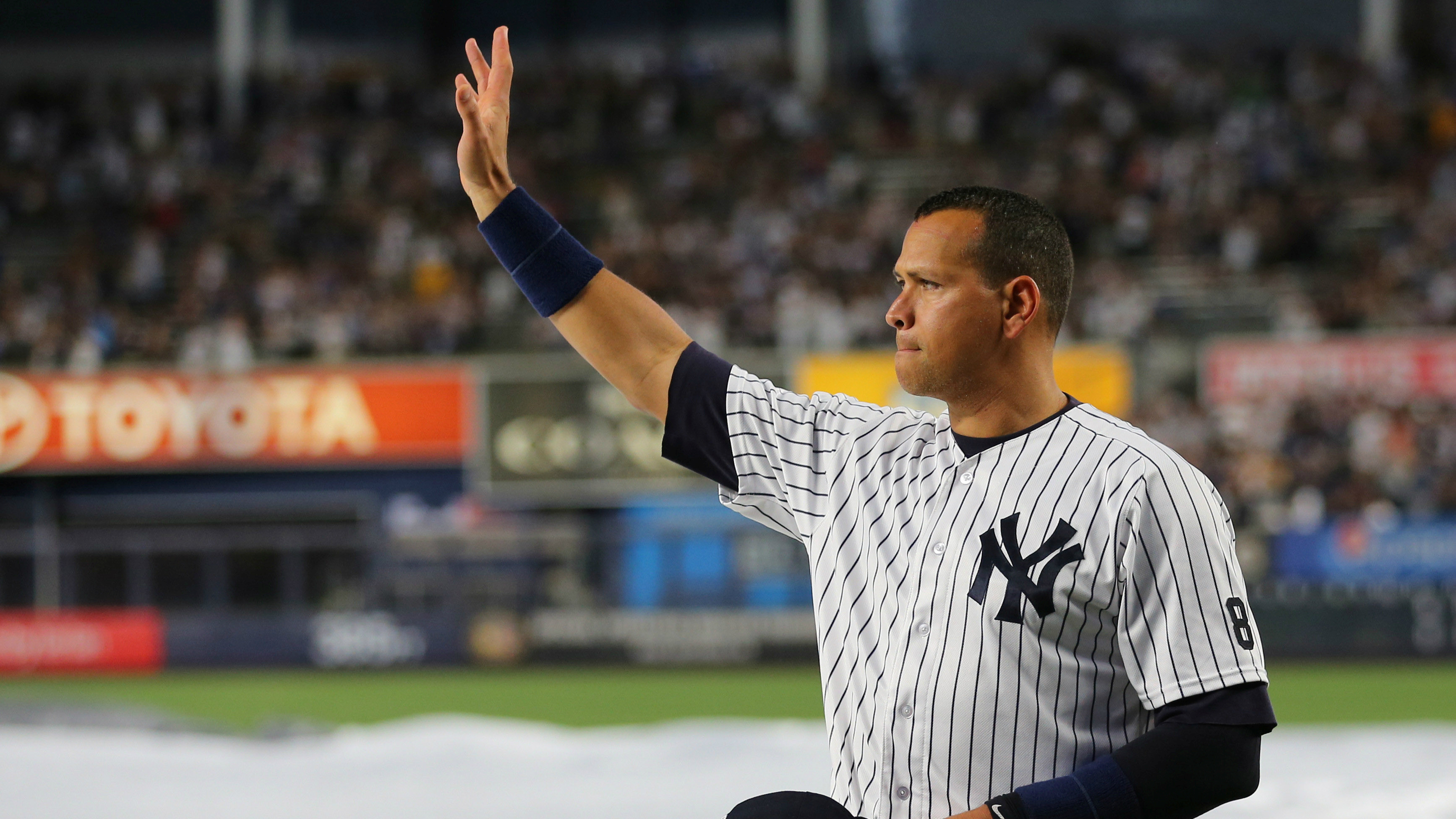The baseball player Alex Rodriguez waving to fans on the day of his final game.