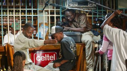 """A cameraman films as actors perform a scene during the making of the film 'Nairobbery' in Nairobi, Kenya, Monday, Aug. 27, 2007. """"We want something that we Kenyans can identify with,"""" said 27-year-old Bonnyface Loppohkoyit, who co-wrote and stars in """"Nairobbery"""", the film about a boy from the slums who joins a gang. He wrote it after a friend was shot by police after his first carjacking; another was lynched by a mob after a theft. While gang violence is not unknown in Hollywood productions, Loppohkoyit says most Westerners have no idea of the grinding poverty millions of Kenyans live in. His main character, Steppa, has to coordinate his girlfriend's visits to their one-room shack with his prostitute sister."""
