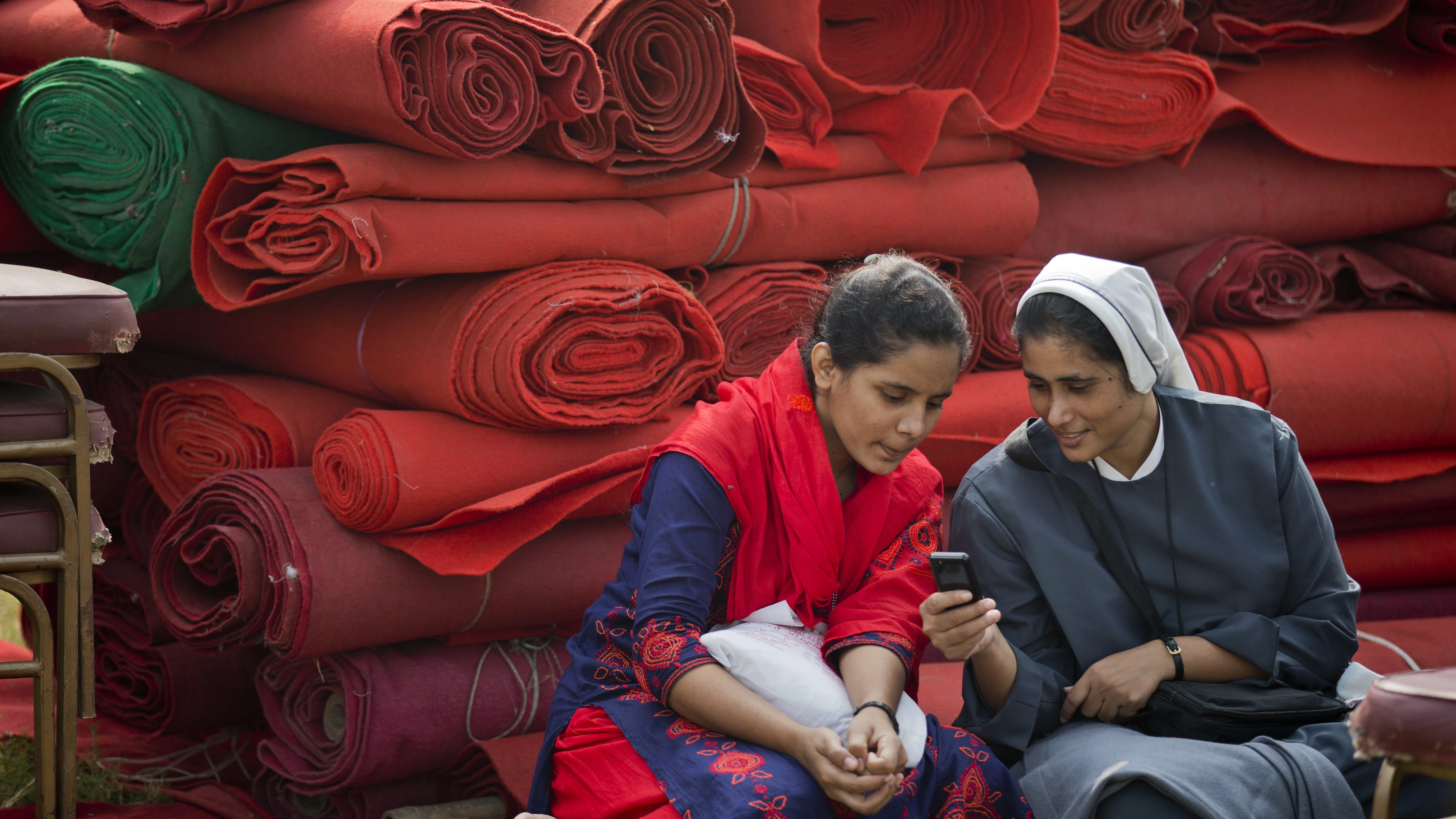 A Bangladeshi Catholic nun checks a mobile phone as workers prepare a makeshift stage where Pope Francis is expected to lead a holy mass in Dhaka, Bangladesh, Wednesday, Nov. 29, 2017. Pope Francis is expected to arrive in Bangladesh Thursday on the second leg of his weeklong South Asia tour. (AP Photo/A.M. Ahad)