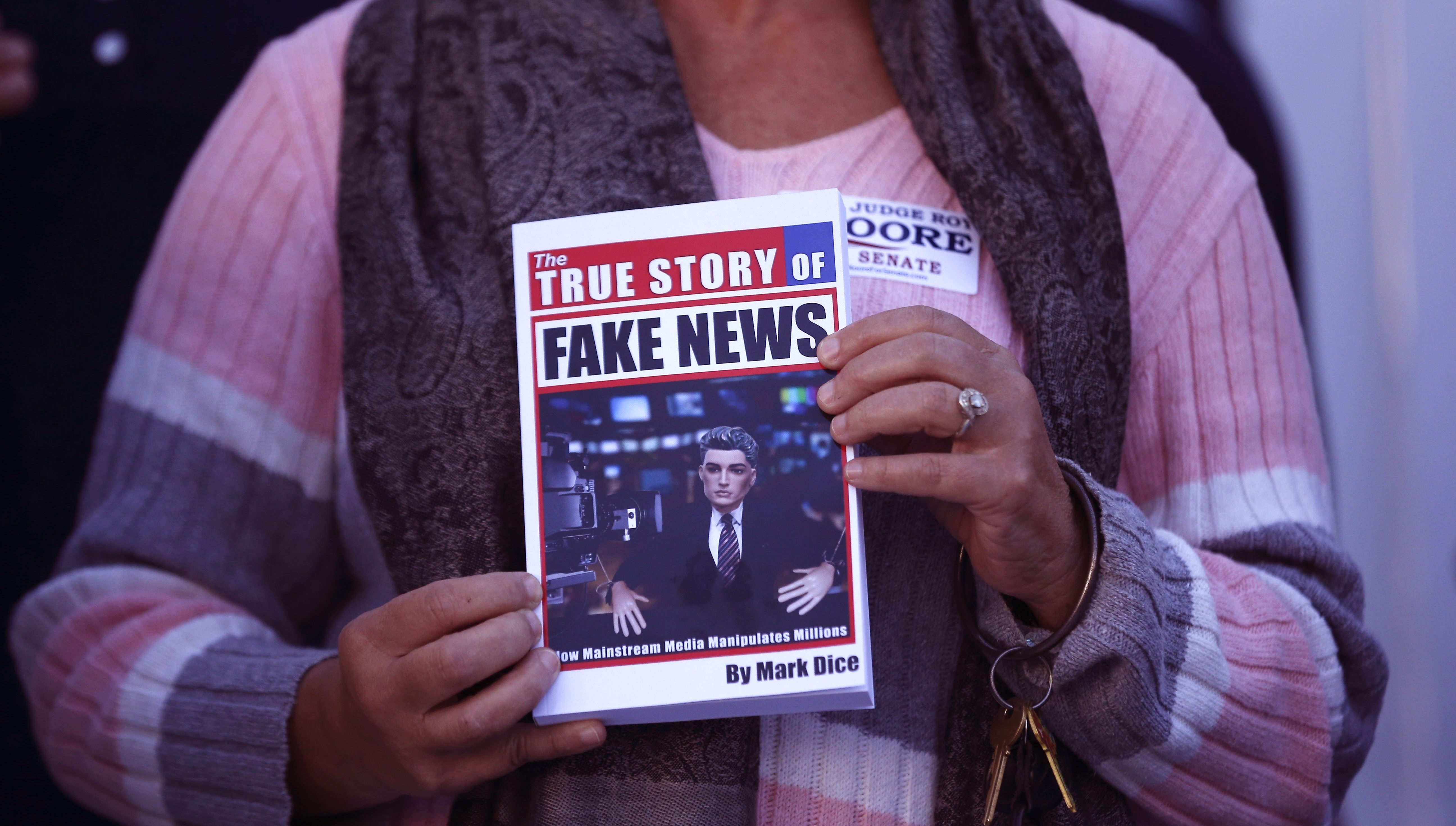 """FILE- In a Nov. 17, 2017 file photo, a supporter holds up a """"Fake News"""" book while Kayla Moore, wife of U.S. Senate candidate Roy Moore, speaks at a press conference in Montgomery, Ala. Would a story that seeks to unpack or drill down on a list of tiresome words and phrases be impactful or a nothingburger? Worse, would it just be tons of fake news? Well, dish all you want, but Northern Michigan's Lake Superior State University on Sunday released its 43rd annual List of Words Banished from the Queen's English for Misuse, Overuse and General Uselessness.(AP Photo/Brynn Anderson_File)"""