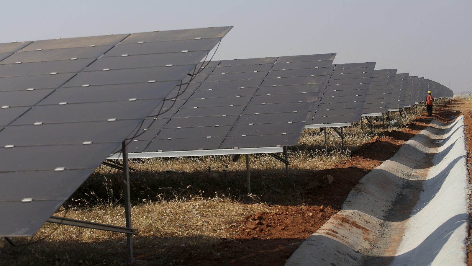 A worker walks past solar panels installed at the Pavagada Solar Park 175 kilometers (109 miles) north of Bangalore, India, Thursday, March 1, 2018. Spanning 5260 hectares (13,000 acres) across five villages and built with investment of INR 16,500 crore (USD $ 2.5 billion), the park that was inaugurated Thursday is expected to produce 2000 megawatts of power according to a press release. (AP Photo/Aijaz Rahi)