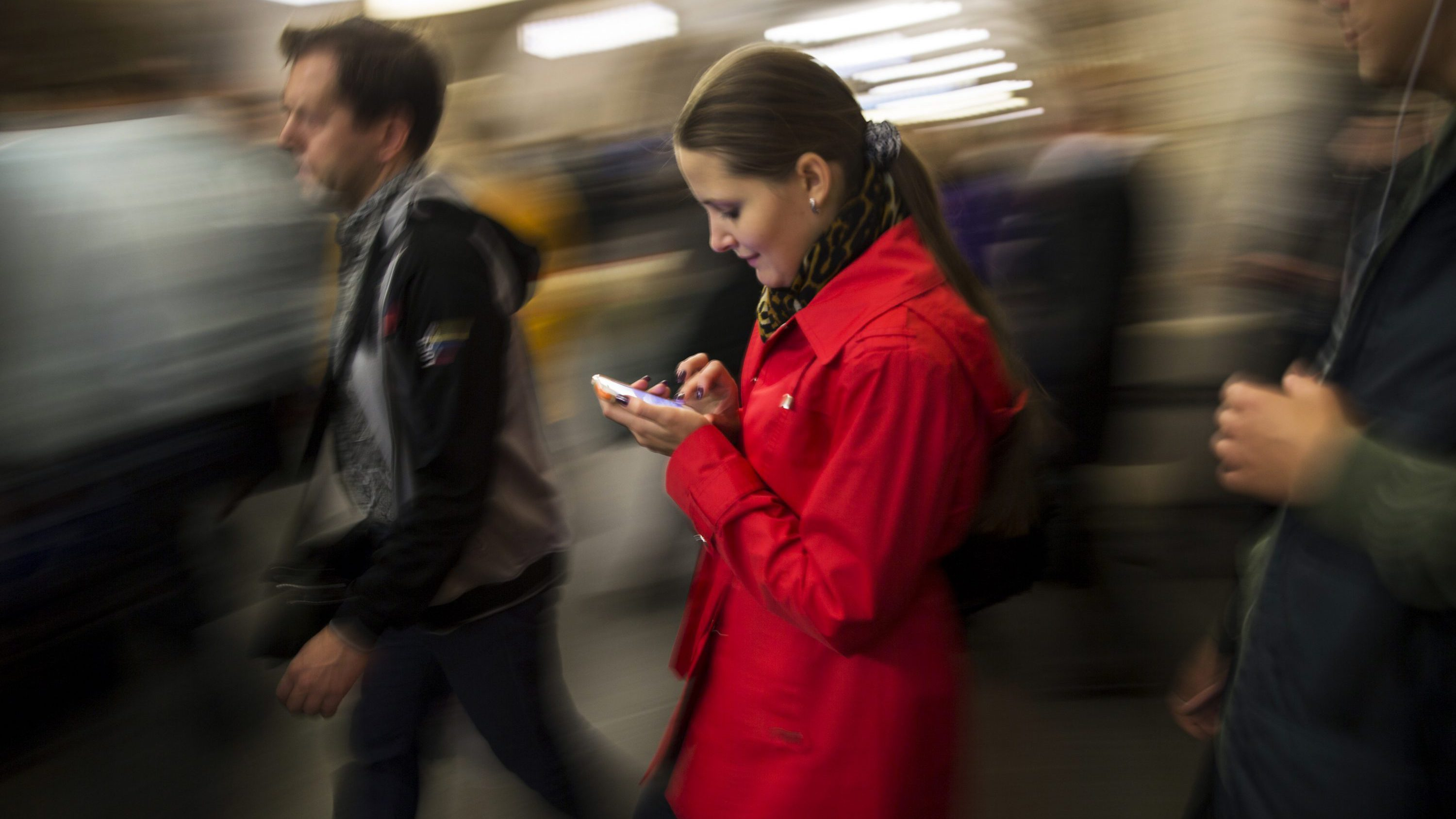 A woman surfs the Internet on her smartphone in Moscow's subway, Russia, Tuesday, Sept. 16, 2014.