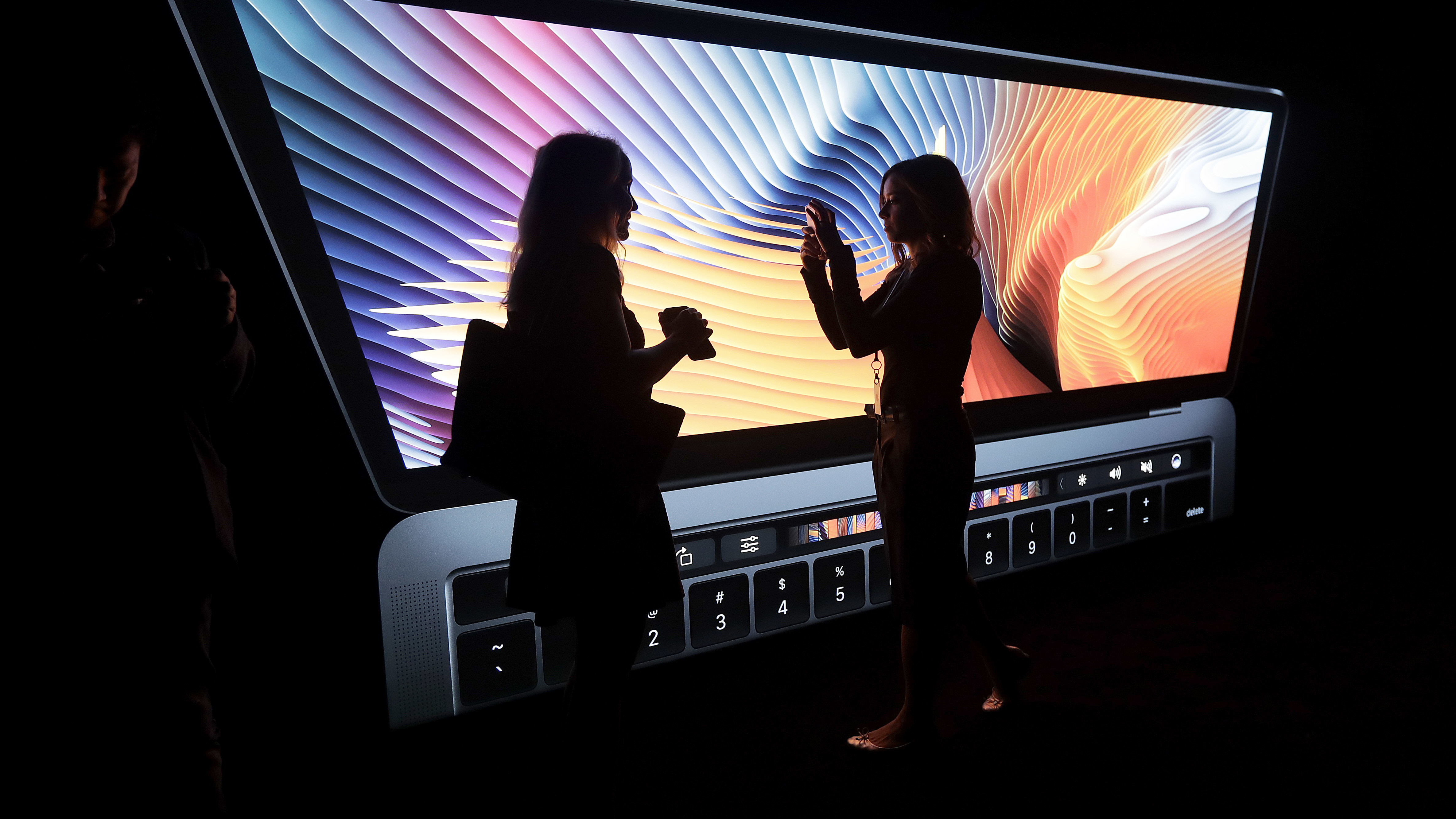Women take photos in front of a large photo displayed of a MacBook computer in a demo room following the announcement of new products at Apple headquarters Thursday, Oct. 27, 2016, in Cupertino, Calif. (AP Photo/Marcio Jose Sanchez)