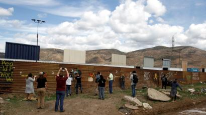 Tourists stand near prototypes for U.S. President Donald Trump's border wall