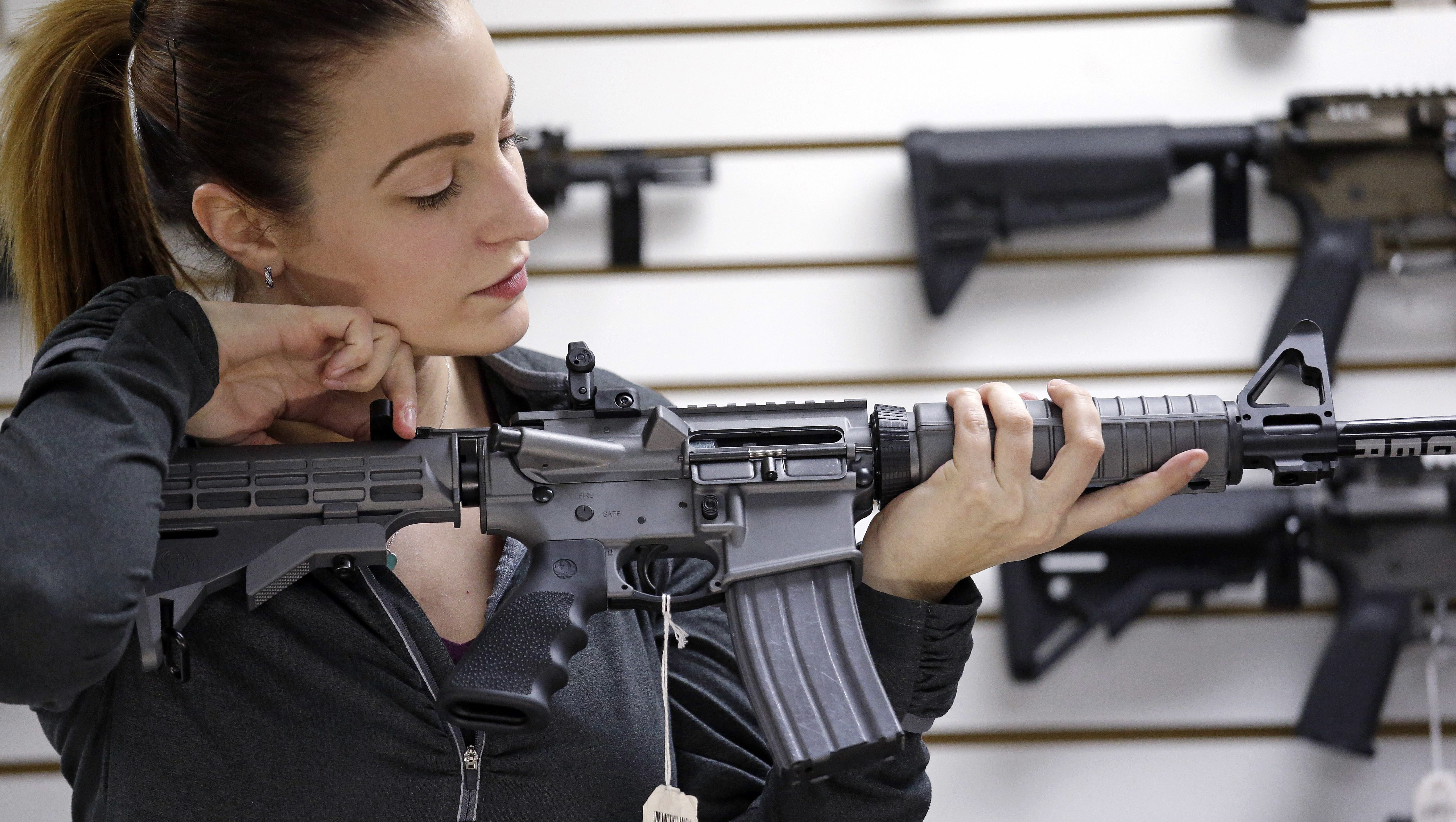 Gun shop owner Tiffany Teasdale-Causer demonstrates a Ruger AR-15 semi-automatic rifle, the same model, though in gray rather than black, used by the shooter in a Texas church massacre two days earlier, Tuesday, Nov. 7, 2017, in Lynnwood, Wash. Gun-rights supporters have seized on the Texas church massacre as proof of the well-worn saying that the best answer to a bad guy with a gun is a good guy with a gun. Gun-control advocates, meanwhile, say the tragedy shows once more that it is too easy to get a weapon in the U.S.
